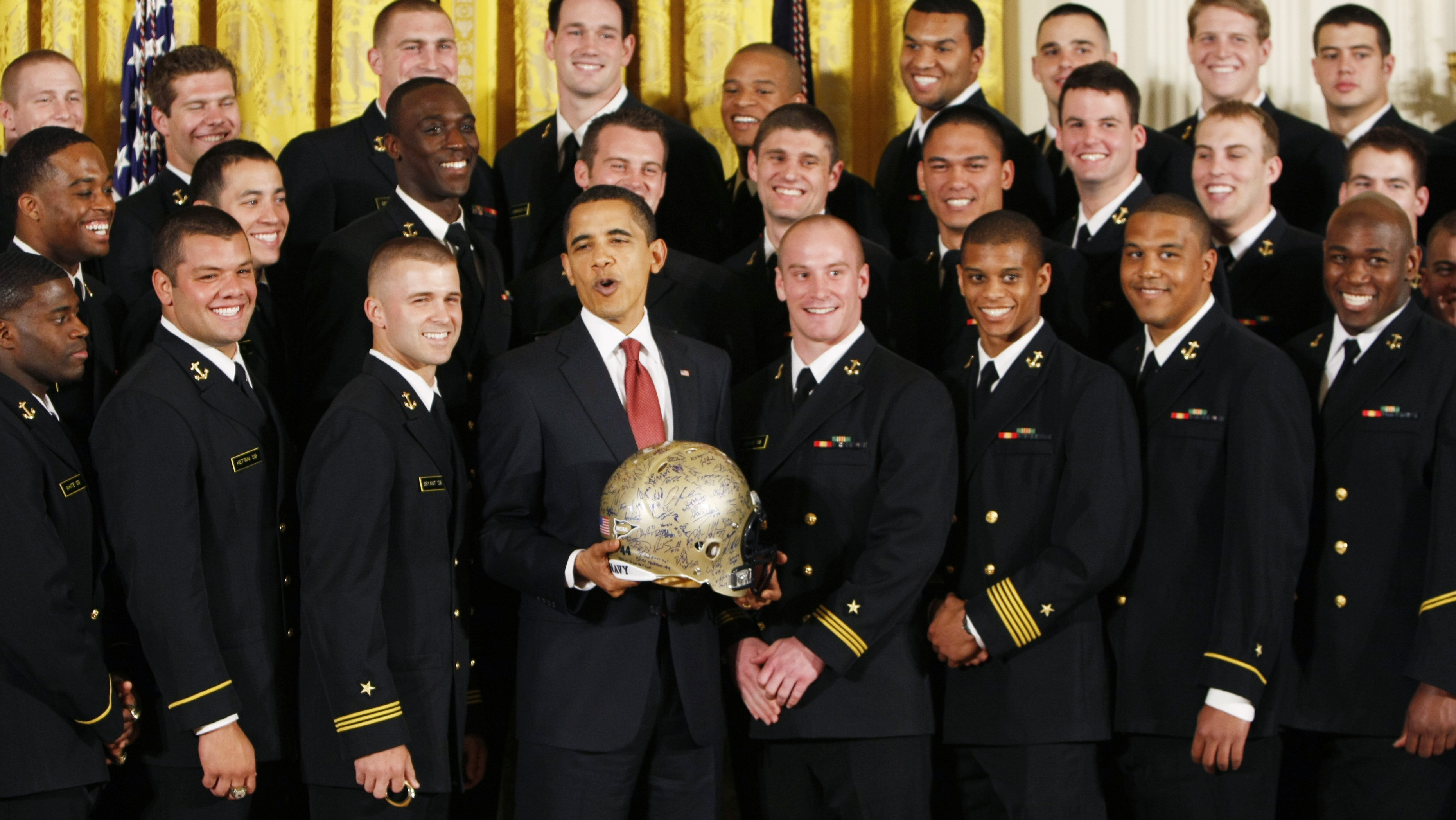 President Barack Obama poses with an autographed helmet given to him in the East Room of the White House in Washington, Tuesday, April 21, 2009, during a ceremony where he presented the Commander in Chief trophy to the U.S. Naval Academy football team. (AP Photo/Gerald Herbert)