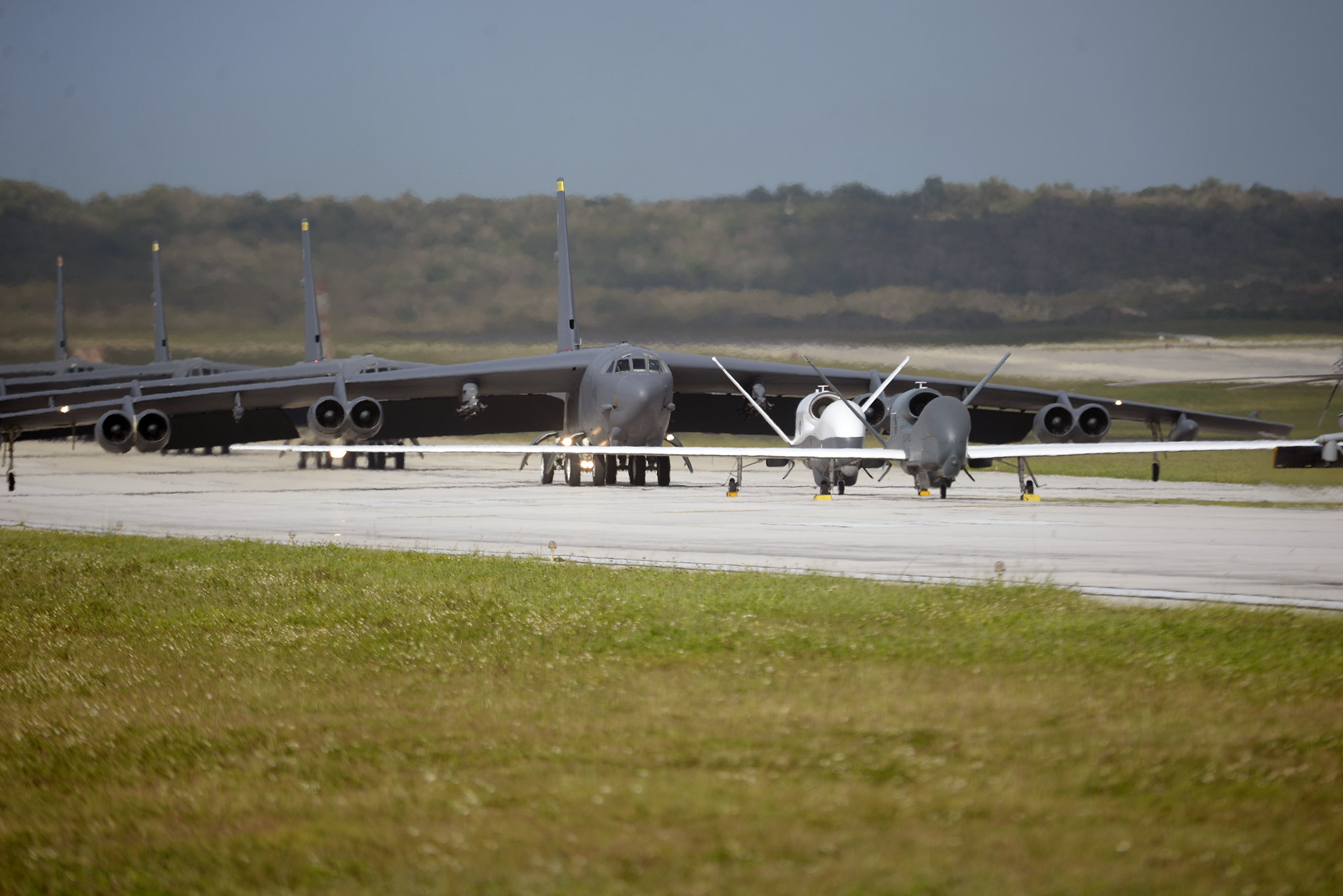 A U.S. Navy MH-60S Knighthawk, U.S. Air Force RQ-4 Global Hawk, Navy MQ-4C Triton, Air Force B-52 Stratofortresses, and KC-135 Stratotankers stationed at Andersen Air Force Base, Guam, perform an