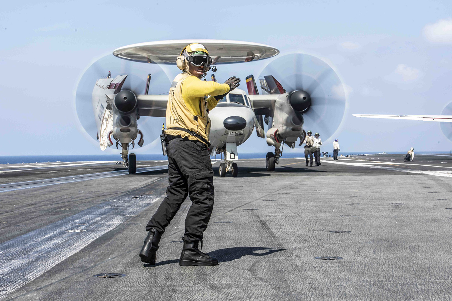 Aviation Boatswain's Mate (Handling) Airman Carlos Gamble, directs an E-2D Hawkeye aboard the Navy's forward-deployed aircraft carrier USS Ronald Reagan (CVN 76) on Sept. 26, 2019, in the South China Sea. (Mass Communication Specialist 2nd Class Tyra M. Campbell/Navy)