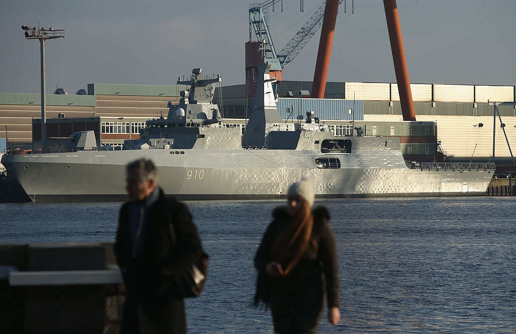 People walk along the shore across from a corvette warship under construction at the ThyssenKrupp Marine Systems shipyard on Jan. 18, 2016, in Kiel, Germany. (Sean Gallup/Getty Images)