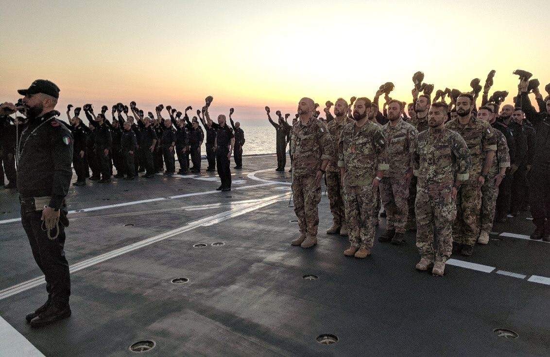 The crew and embarked Marines onboard the Italian FREMM Alpino participate in a weekly evening colors ceremony on the flight deck. (David B. Larter/Staff)