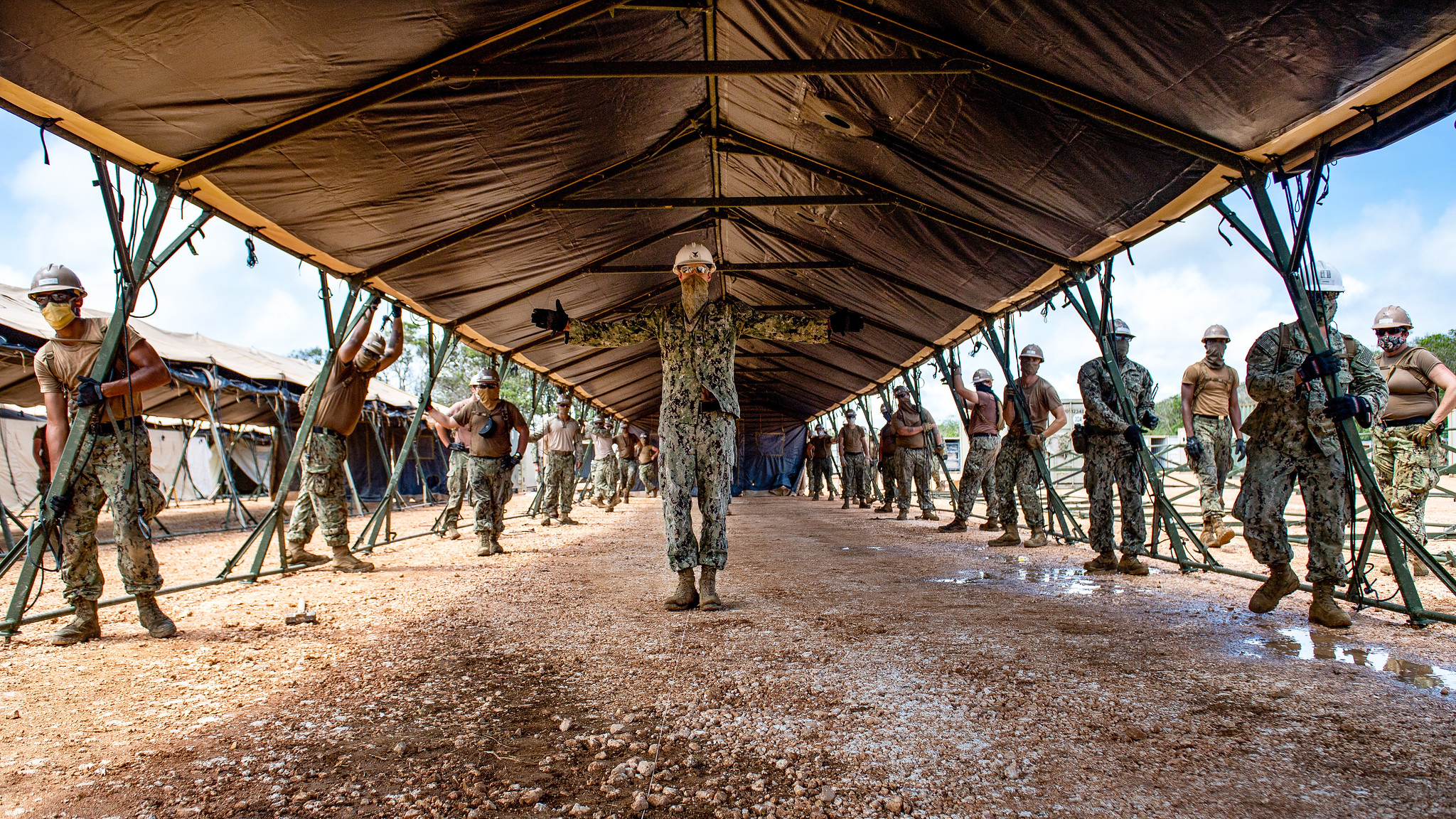 Sailors assigned to Task Force 75.5 prepare to lift a tent during construction of a 150-bed expeditionary medical facility at Naval Base Guam on April 21, 2020. (Mass Communication Specialist 1st Class Julio Rivera/Navy)