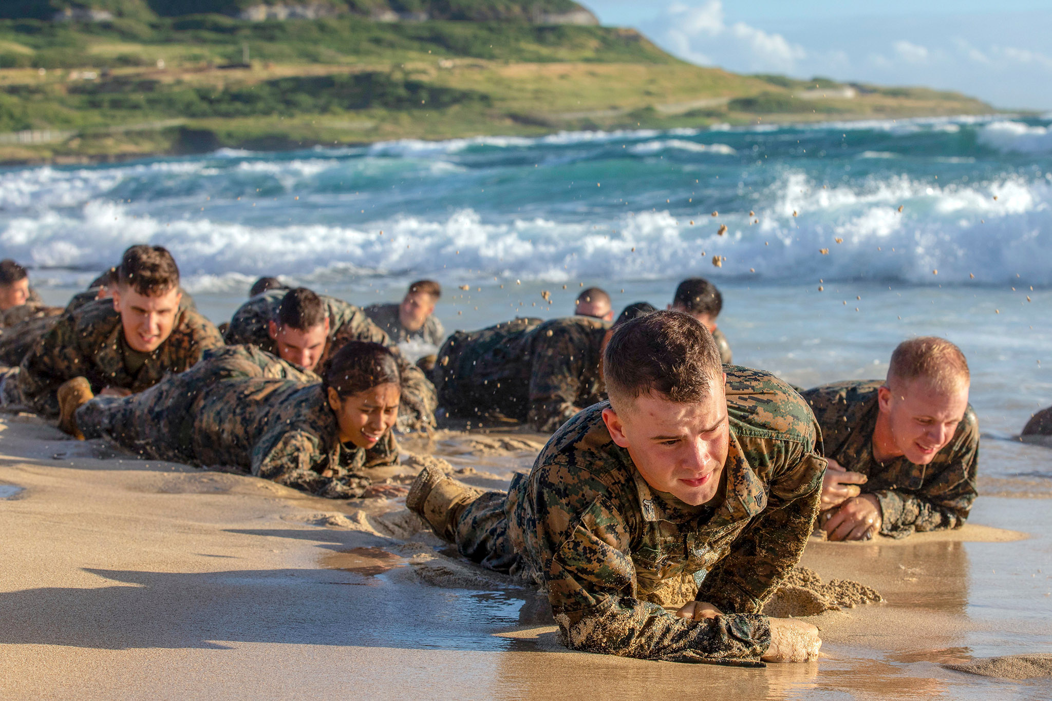 Marines attending the Corporals Course at Marine Corps Base Hawaii low crawl on Fort Hase Beach during a small unit leadership evaluation on Dec. 12, 2018, in Hawaii. (Sgt. Jesus Sepulveda Torres/Marine Corps)