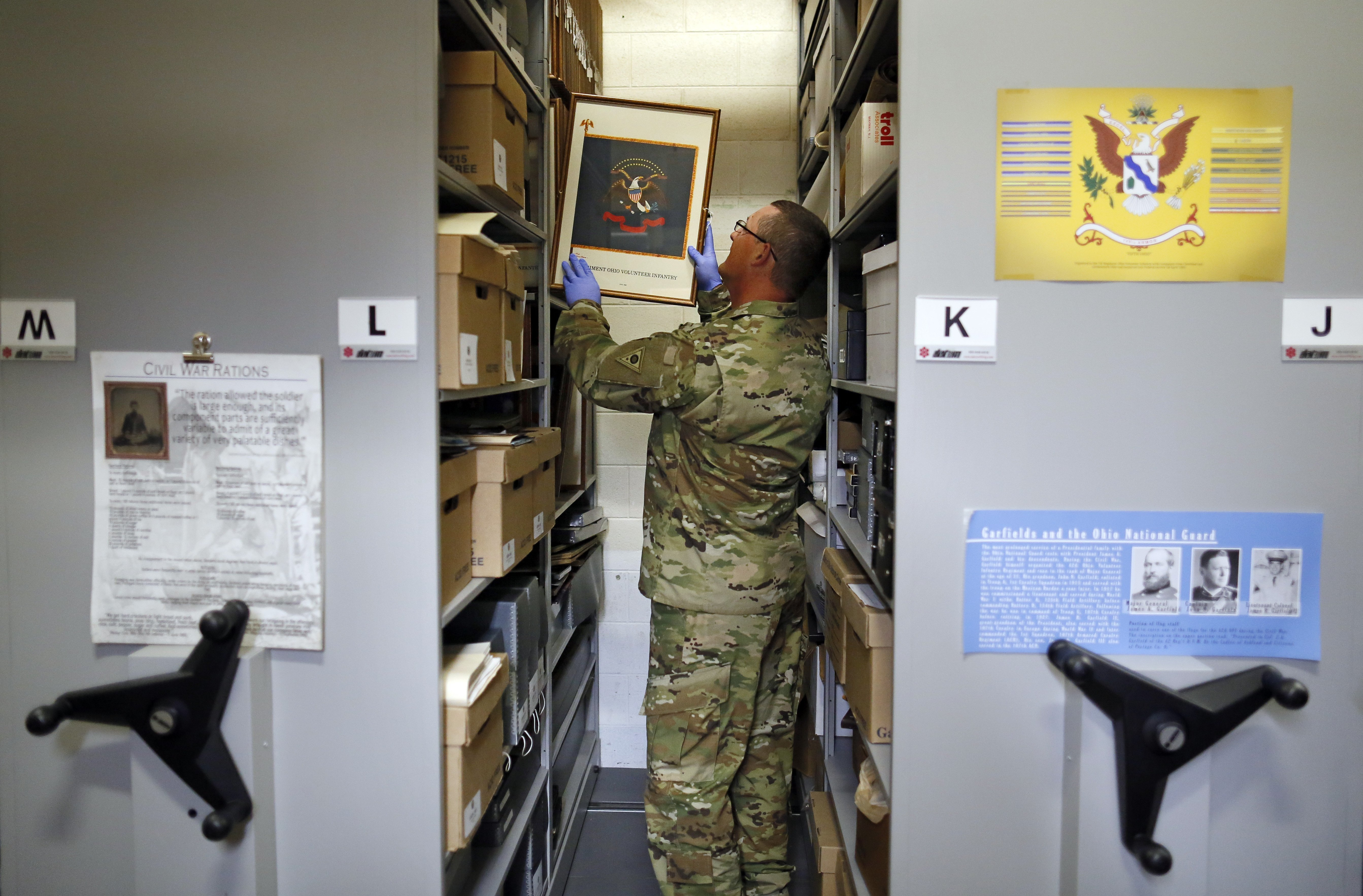 In this July 17, 2018, photo, Sgt. 1st Class Josh Mann, the Ohio Army National Guard historian, files away an artist's rendering of an infantry battle flag inside the Beightler Armory in Columbus, Ohio. The Ohio National Guard is celebrating its 230 years of service. (Adam Cairns/The Columbus Dispatch via AP)