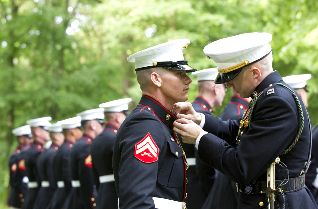 A U.S. Marine Corps officer, right, helps an enlisted Marine adjust his tunic as they participate in a commemoration at the American Marine Memorial in Belleau Wood prior to a service at the Aisne-Marne American Cemetery in Belleau, France, Sunday, May 27, 2018. (Virginia Mayo/AP)