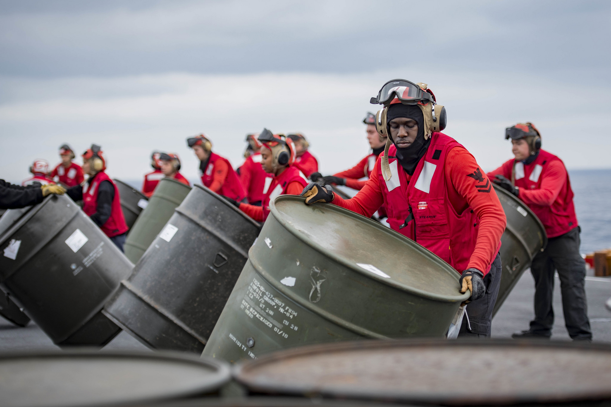 AO2 Adarryl Chaney, from New Orleans, and other weapons department Sailors move barrels containing ammunition to staging areas in preparation of an ammunition offload aboard the aircraft carrier USS George H.W. Bush (CVN 77). The ship is underway conducting sustainment exercises to maintain carrier readiness. (MC3 Joe Boggio/Navy)