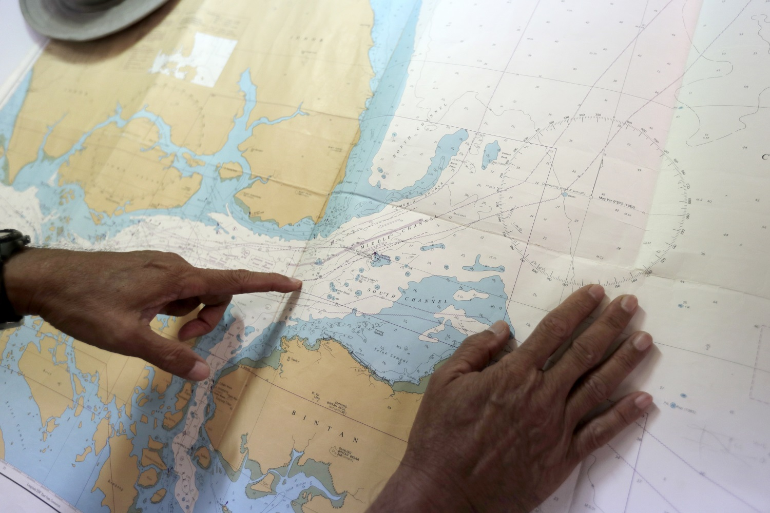 Tan Hua Chiow, a retired Singapore naval officer, shows a naval chart and explains to The Associated Press the flow of traffic at sea around the Strait of Singapore on Aug. 22, 2017, in Singapore. (Wong Maye-E/AP)