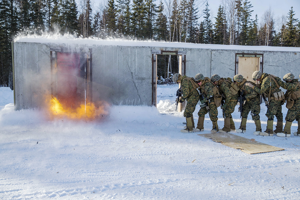 Marines with Weapons Company, 3rd Battalion, 8th Marine Regiment, 2nd Marine Division brace for an explosion during a breaching exercise on Joint Base Elmendorf-Richardson (JBER), Ala., March 1, 2018. Marines with Kilo Co. conduct squad attacks during ISBC for Arctic Edge-18 in order to enhance readiness and combat effectiveness in an extreme cold weather environment. (Lance Cpl. Tanner Seims/Marines)