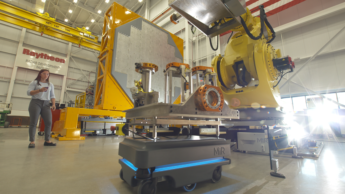 An automated guided vehicle brings parts and tools over to the robotic arm that helps build enormous SPY-6 radars in Raytheon's new state-of-the-art radar development facility which officially opened in August 2018. The company broke ground on the new facility in May 2017. (Photo courtesy of Raytheon)