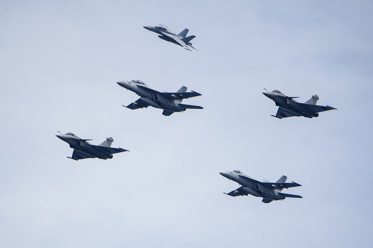 F/A-18 Super Hornets, assigned to Carrier Air Wing One, and French Dassault Rafale M fighters fly over the Nimitz-class aircraft carrier Harry S. Truman. Truman is deployed as part of an ongoing rotation of U.S. forces supporting maritime security operations in international waters around the globe. (U.S. Navy)
