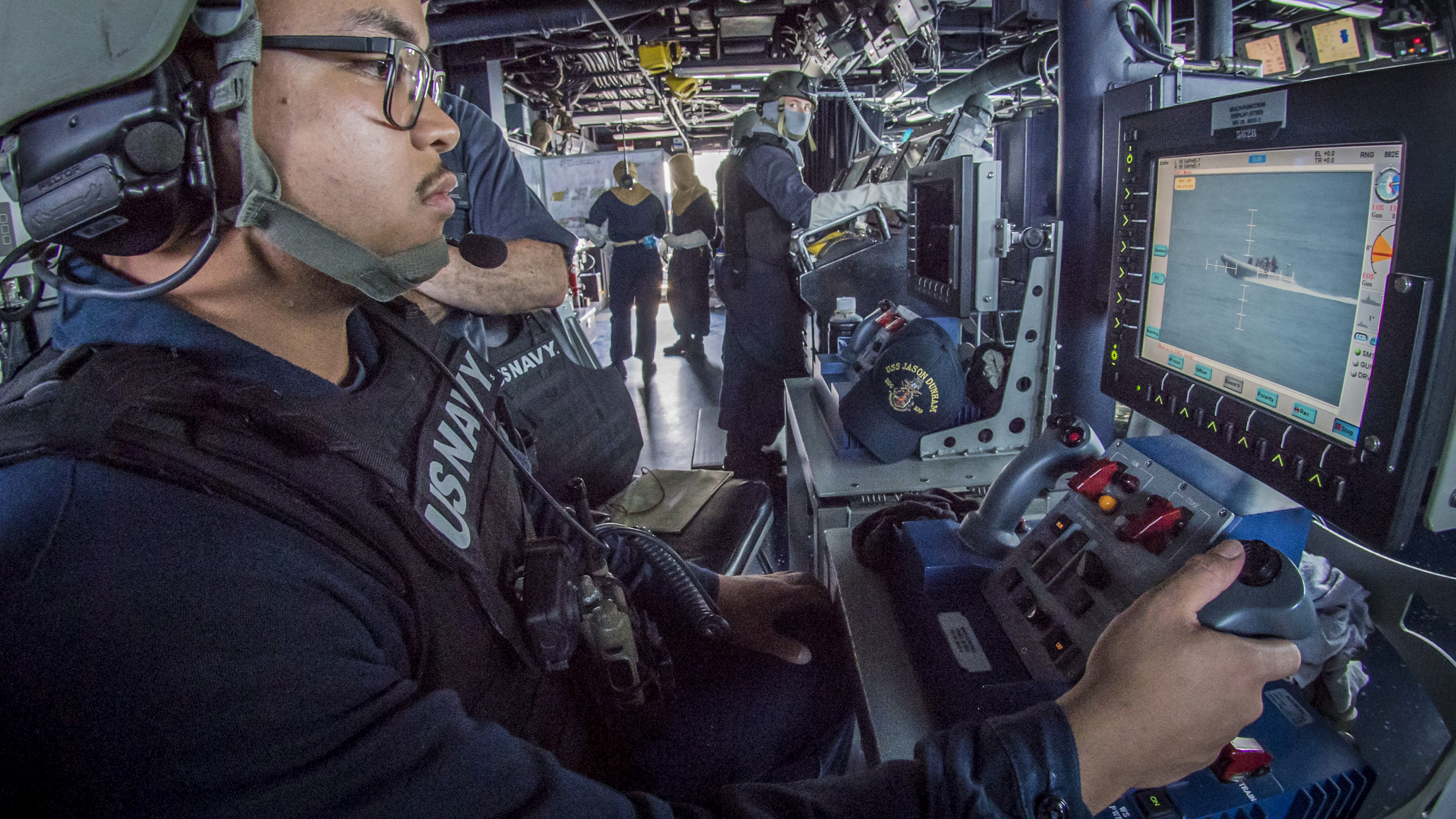 GunnerÕs Mate Seaman Mason Mendiola tracks a small boat with a remote operating console for the Mark 38 25 mm machine gun system during a general quarters exercise aboard the guided-missile destroyer USS Jason Dunham (DDG 109). Jason Dunham is deployed to the U.S. 5th Fleet area of operations in support of naval operations to ensure maritime stability and security in the Central Region, connecting the Mediterranean and the Pacific through the western Indian Ocean and three strategic choke points. (MC3 Jonathan Clay/Navy)