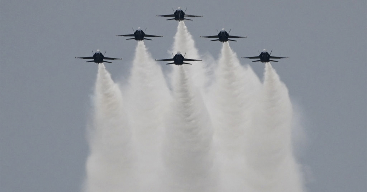 The Blue Angels (six F-18s) fly overhead as people gather on the National Mall during the