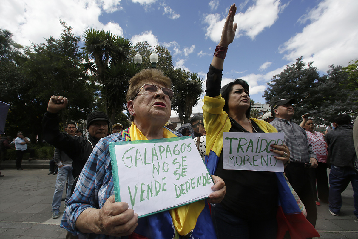 """A woman holds a sign with a message that reads in Spanish; """"Galapagos is not to be sold, but to be defended,"""" during a protest against the government's plan to allow the U.S. military to use a Galapagos island for aircraft on anti-drug trafficking flights, outside the government palace in Quito, Ecuador, Monday, June 17, 2019. (Dolores Ochoa/AP)"""