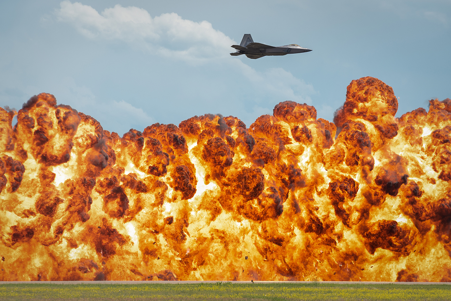 "A 1,000-foot wall of fire explodes below the F-22 Raptor during a high-speed pass maneuver at the ""Mission Over Malmstrom"" open house event in Great Falls, Mont., July 14, 2019. (2nd Lt. Samuel Eckholm/Air Force)"