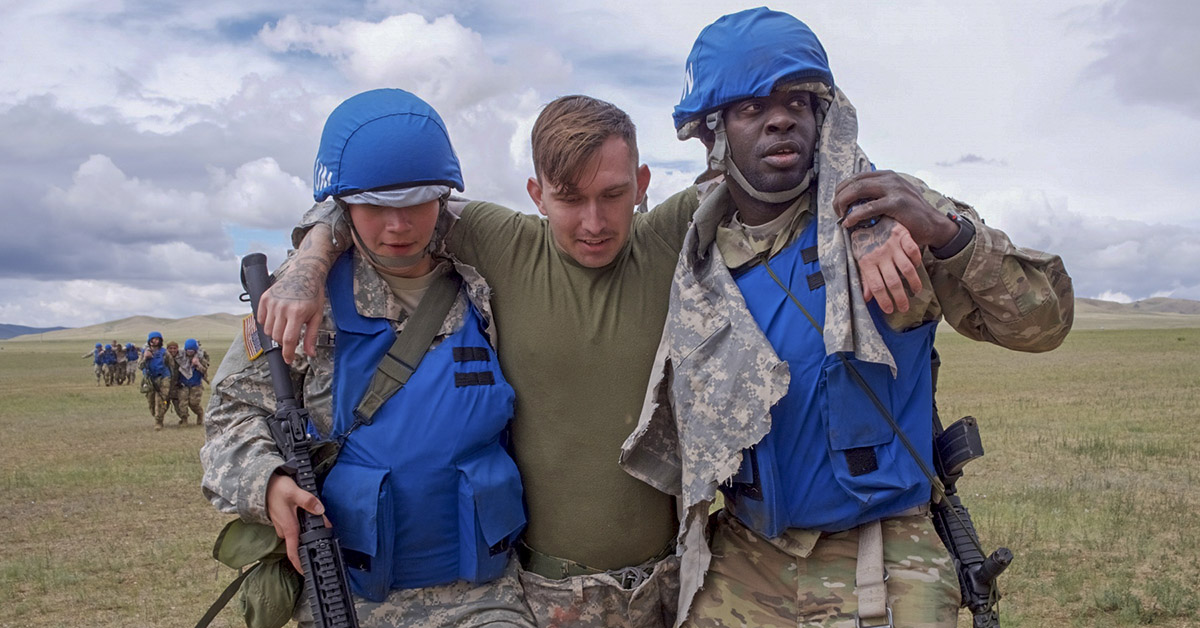 Alaska Army National Guard Spc. Dana Haddox and Spc. Jahmoi Hodge, both members of the platoon representing the 297th Regional Support Group, evacuate simulated casualty Navy HC3 John Bustamonte, III Marine Expeditionary Force, June 17, 2018, during Tactical Combat Casualty Care training at Five Hills Training Area, Mongolia, as part of Khaan Quest 2018. The purpose of Khaan Quest is to gain United Nations training and certification for the participants through the conduct of realistic peace support operations, to include increasing and improving UN PKO interoperability and military relationships among the participating nations. (Sgt. David Bedard/Army)
