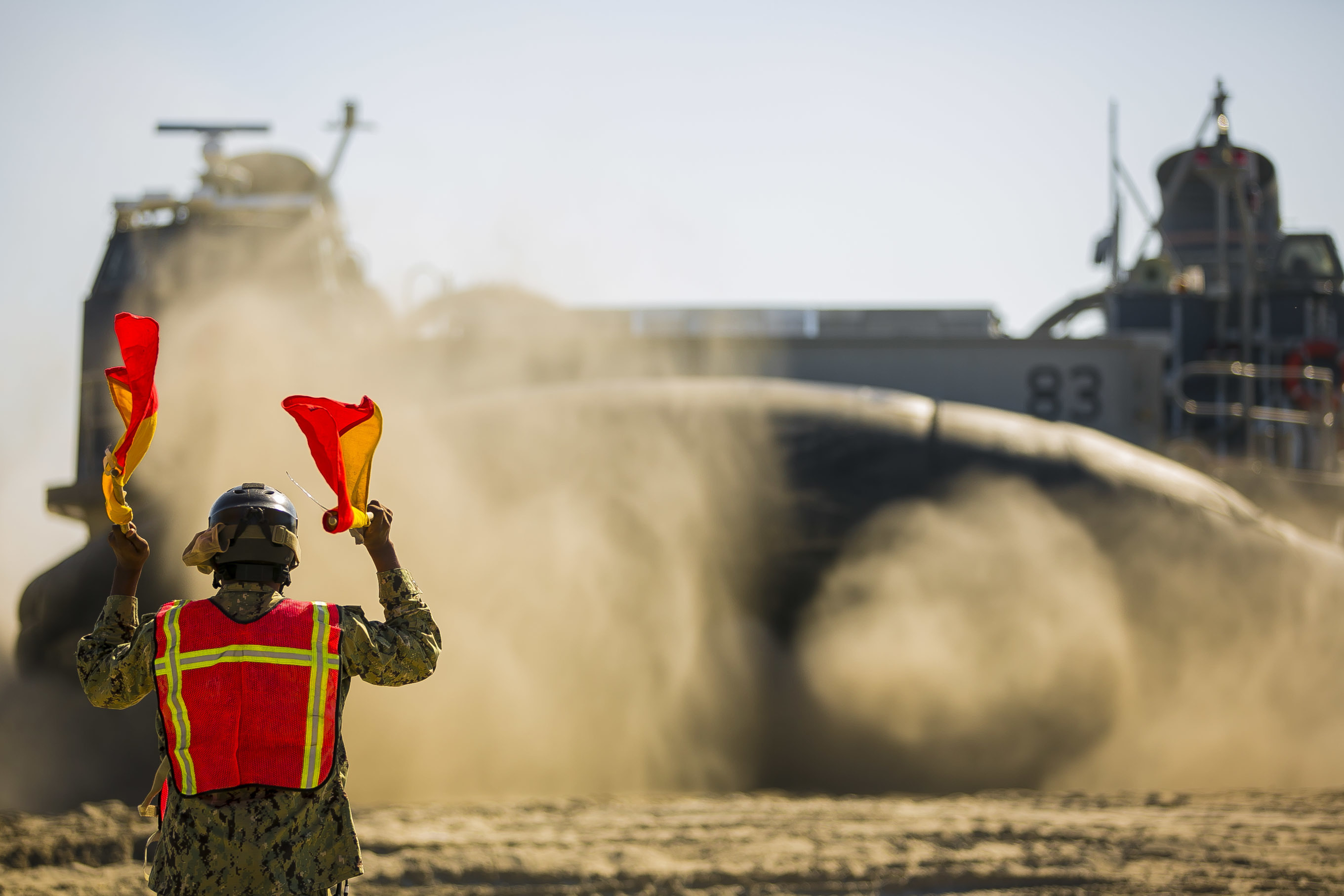A U.S. Navy sailor signals Landing Craft, Air Cushion 83, to embark on the amphibious assault ship USS Iwo Jima (LHD-7) as part of a Composite Training Unit Exercise (COMPTUEX) at Onslow Beach. (Staff Sgt. Dengrier M. Baez/Marine Corps)