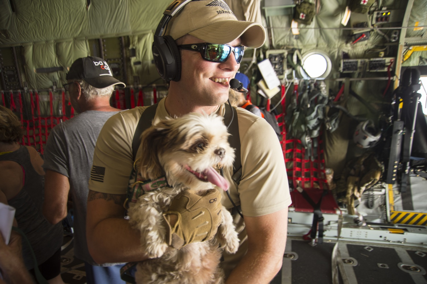 Capt. William Hall, HC-130 pilot with the 102nd Rescue Squadron, helps bring an evacuee's service dog on board an HC-130 headed to San Juan, Puerto Rico, on Sept. 10, 2017. (Staff Sgt. Erin Mills/Air Force)