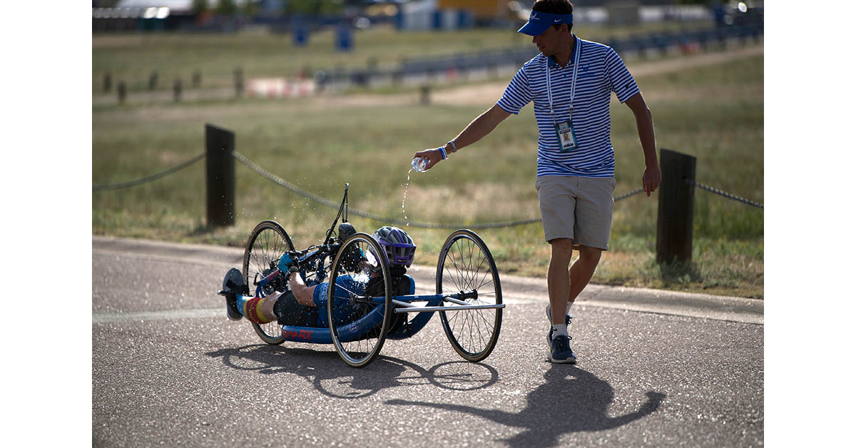 Air Force Coach Aaron Moffett pours water over an athlete during the 2018 DoD Warrior Games cycling competition at the Air Force Academy in Colorado Springs, Colo. June 6, 2018. (EJ Hersom/DoD)