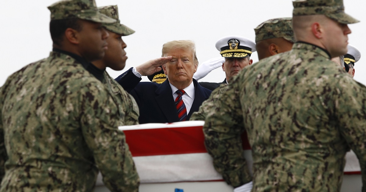 President Donald Trump salutes as a U.S. Navy carry team moves a transfer case containing the remains of Scott A. Wirtz Saturday at Dover Air Force Base, Del. Wirtz, a civilian and former Navy SEAL from St. Louis was killed Jan. 16 in a suicide bomb attack in Manbij, Syria. (Patrick Semansky/AP)
