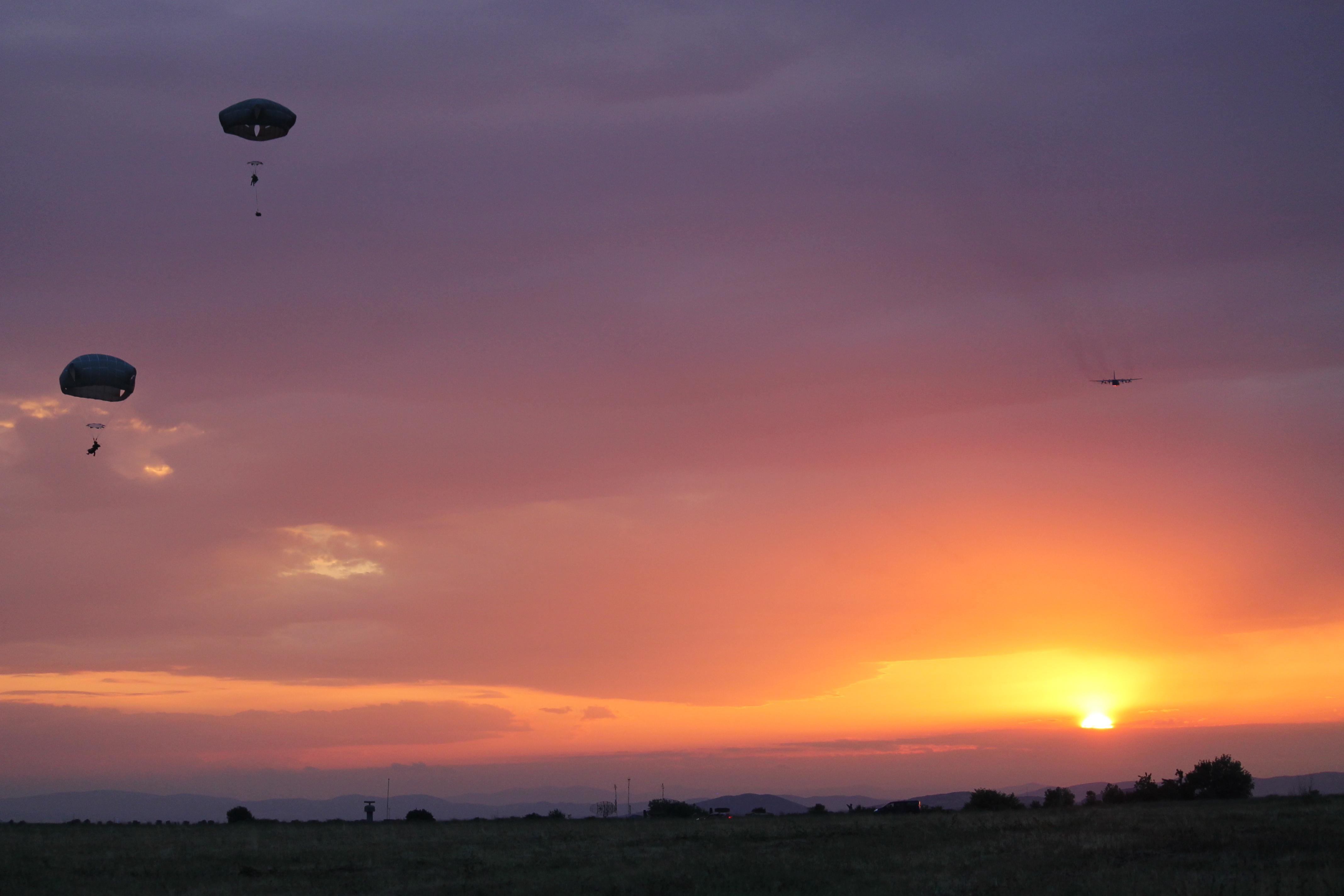 The last of the paratroopers land as a C-130 flies off into the sunset. While there were a dozen injuries that required temporary hospitalization as the result of a jump in Romania, also part of the Saber Guardian exercise, the Bezmer jump had minimal injuries. (Jen Judson/Staff)