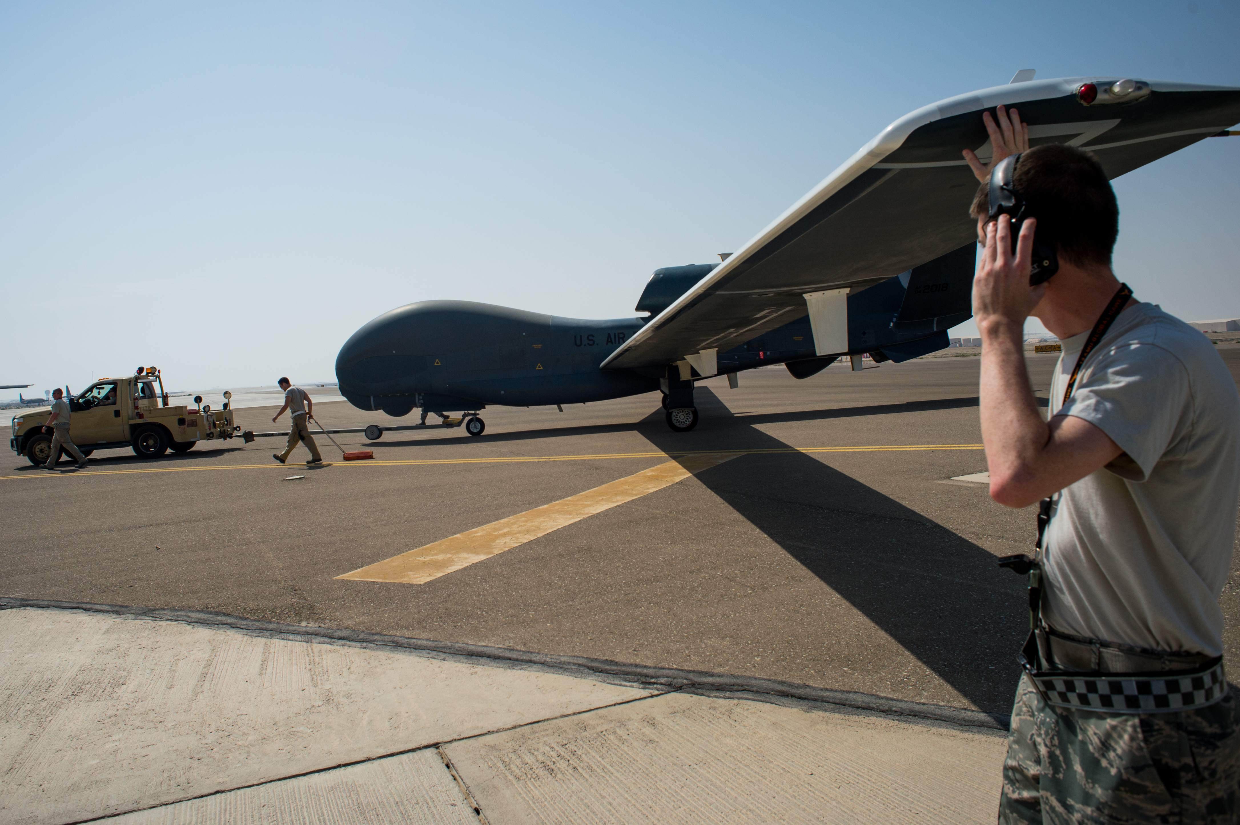 Members of the 380th Expeditionary Maintenance Squadron complete post-flight checks on an EQ-4 Global Hawk equipped with a battlefield airborne communications node at an undisclosed location in Southwest Asia on April 1, 2017. (Senior Airman Tyler Woodward/U.S. Air Force)