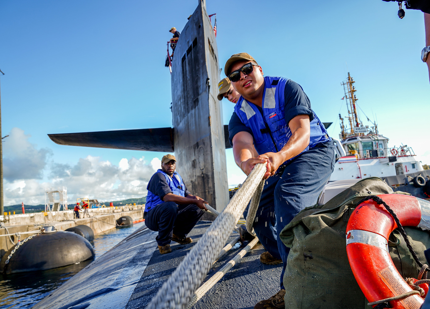 Sailors assigned to the Los Angeles-class fast attack submarine USS Oklahoma City (SSN 723) handle line Sept. 24, 2019, as the boat moors pierside at Apra Harbor, Guam, following a family day cruise. (Mass Communication Specialist 2nd Class Kelsey J. Hockenberger/Navy)