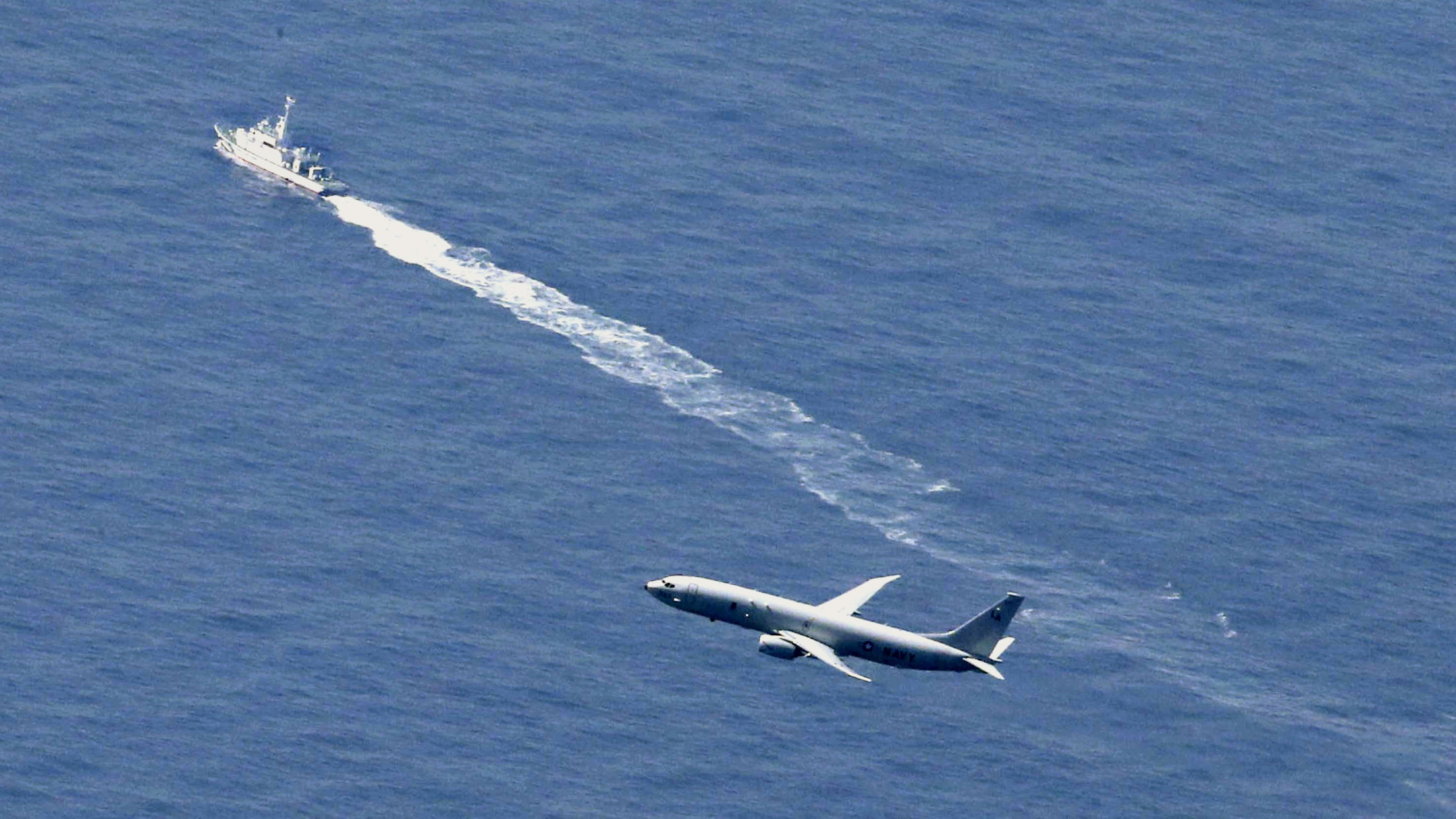 A Japan Coast Guard's vessel and U.S. military plane search for a Japanese fighter jet, in the waters off Aomori, northern Japan, Wednesday, April 10, 2019. The Japanese air force F-35 stealth fighter crashed into the Pacific Ocean during a night training flight and parts of the jet were recovered, the defense ministry said Wednesday. (Kyodo News via AP)