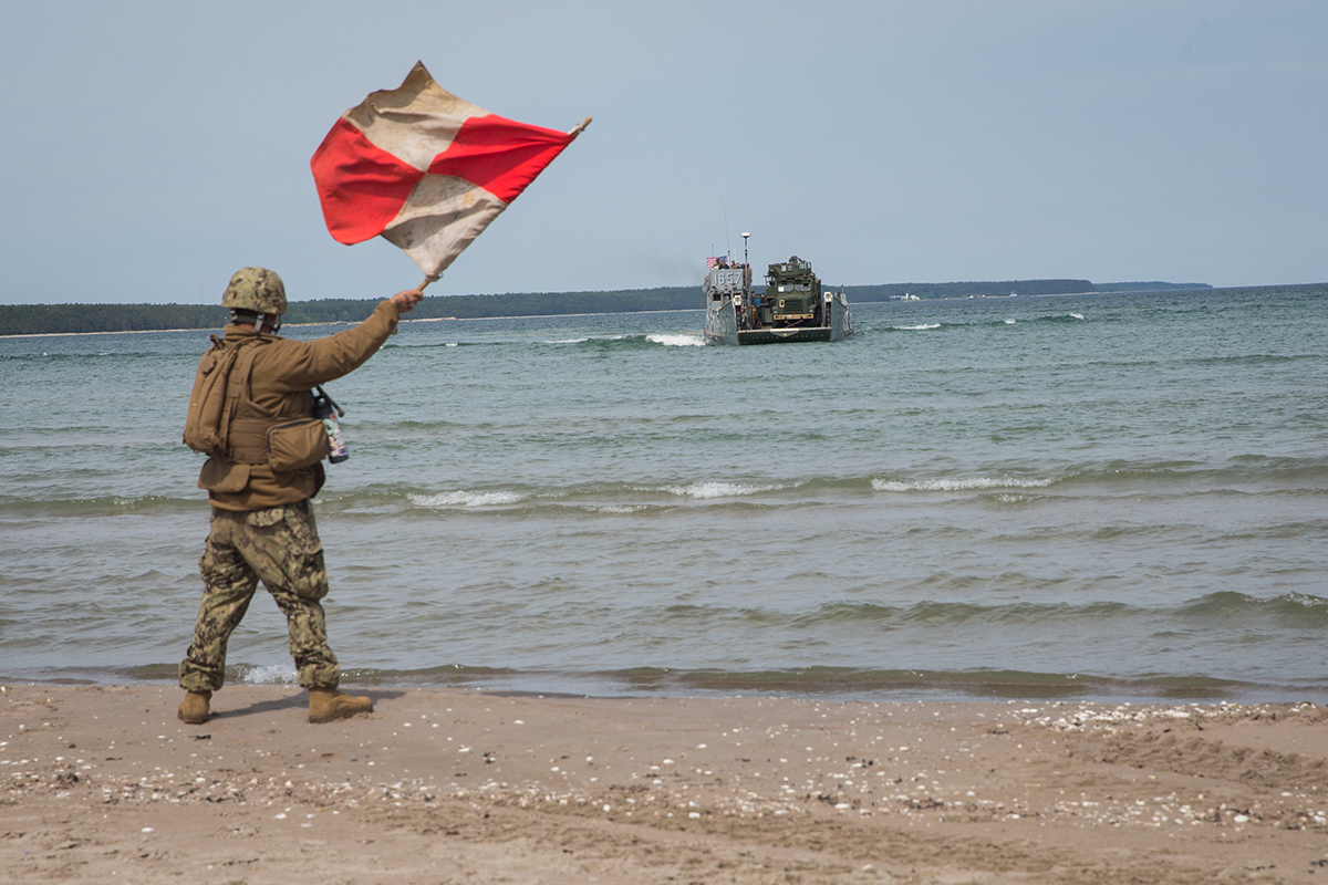 A sailor signals a U.S. Navy landing craft, utility on June 12, 2019, to offload tactical vehicles during Exercise Baltic Operations 2019 in Kallaste, Estonia. (Cpl. Abrey Liggins/Marine Corps)