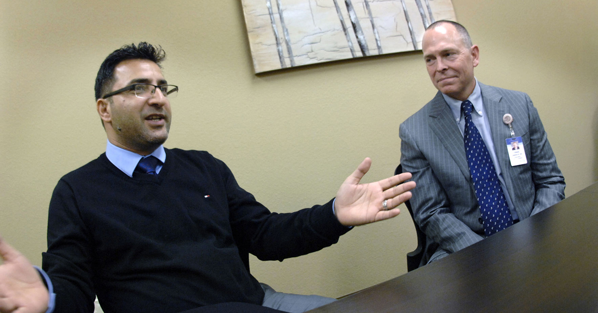 This Feb. 19, 2018 photo shows Dr. Firas Egal, left, and Dr. Craig Lambrecht, executive vice president at Sanford Health, in Bismarck, N.D. After serving as an important resource for American troops in Iraq, Egal fled to the United States for safety. He applied for asylum, and became an American citizen in 2014. Egal and Lambrecht have recently connected in Bismarck, as Egal applies for medical residencies. (Mike McCleary/The Bismarck Tribune via AP)