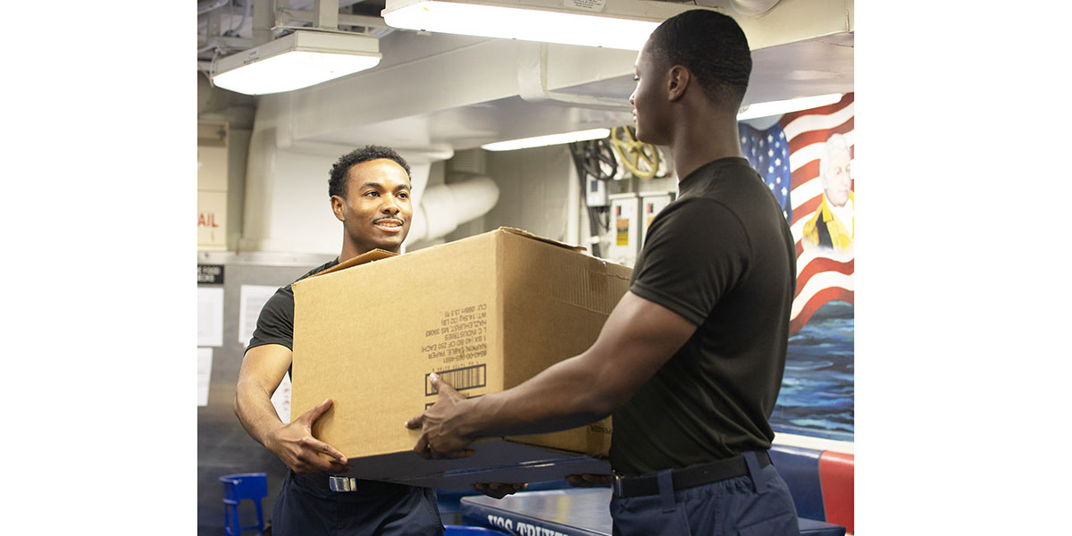 Operations Specialist 3rd Class Warren Maxwell (left) and Operations Specialist Seaman Demetrus Jones, assigned to Arleigh Burke-class destroyer USS Truxtun (DDG 103), demonstrate the operational de-blousing capability of the flame-resistant, two-piece organizational clothing prototype. (Mass Communication Specialist 2nd Class Stacy M. Atkins Ricks/Navy)