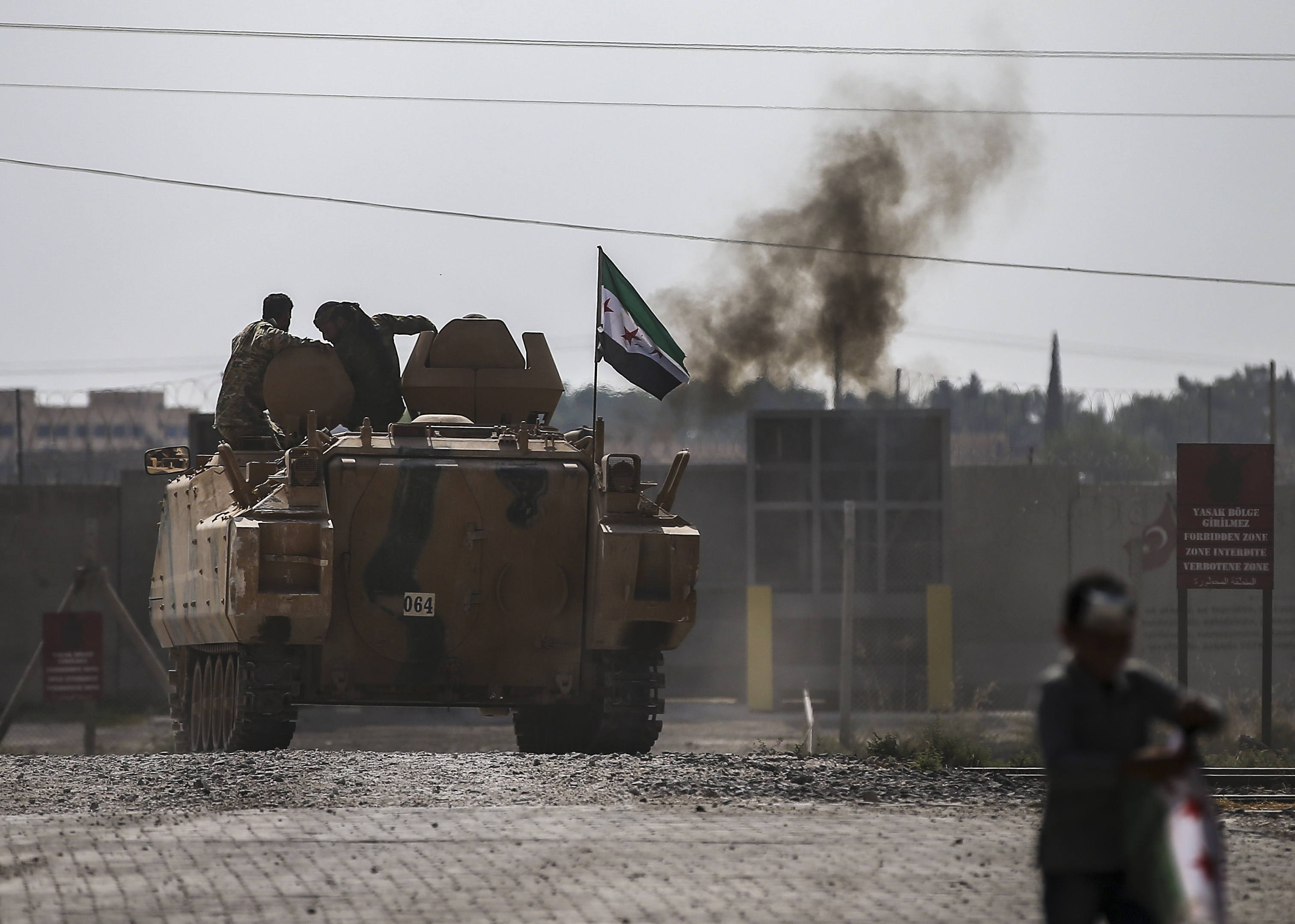 Turkish-backed Syrian opposition fighters on an armoured personnel carrier drive to cross the border into Syriaon Oct. 18, 2019. (Emrah Gurel/AP)