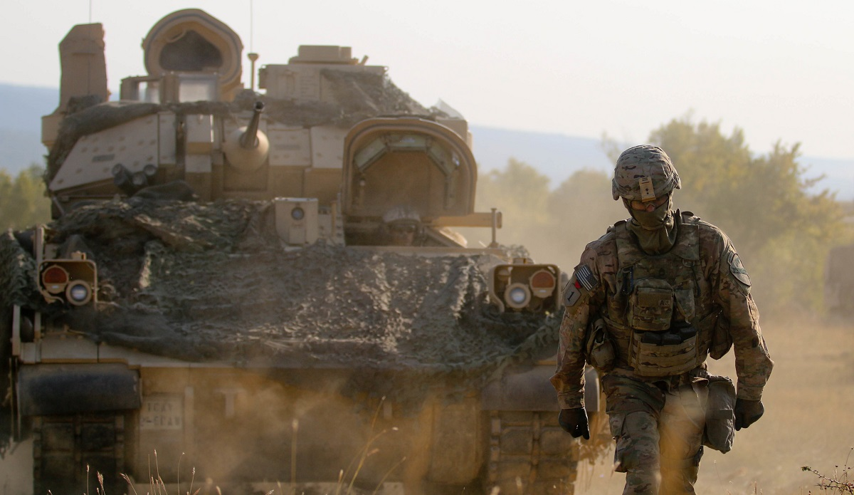 U.S. Army Sgt. 1st Class Chez Carter, assigned to Alpha Company, 2nd Battalion, 5th Cavalry Regiment, 1st Armored Brigade Combat Team, 1st Cavalry Division ground guides a M2A3 Bradley Fighting Vehicle during a Table XII Live Fire Exercise, Novo Selo Training Area, Bulgaria, August 23, 2018. This exercise is in support of Atlantic Resolve, an enduring training exercise between NATO and U.S. Forces. (U.S. Army National Guard photo by Sgt. Jamar Marcel Pugh, 382nd Public Affairs Detachment/ 1st ABCT, 1st CD/Released)