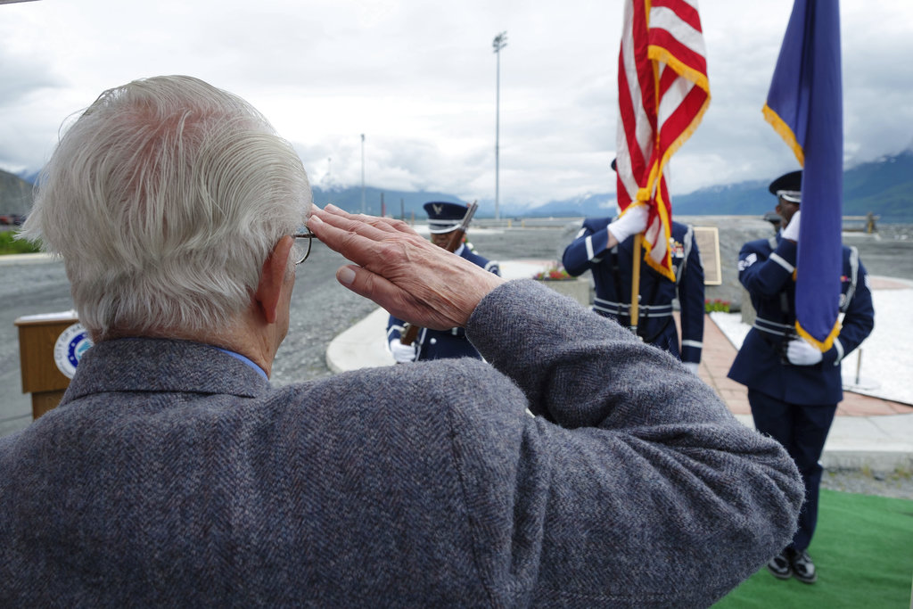 Former Alaska Air National Guard member Chuck Volanti salutes the honor guard at a plaque dedication ceremony Saturday, June 23, 2018, in Valdez, Alaska. The memorial plaque, which Volanti has worked for years to realize, honors four Alaska National Guard members killed in April 1964 while conducting a humanitarian mission after the second most powerful earthquake ever destroyed the town. (David Lienemann/Office of Alaska Gov. Bill Walker via AP)