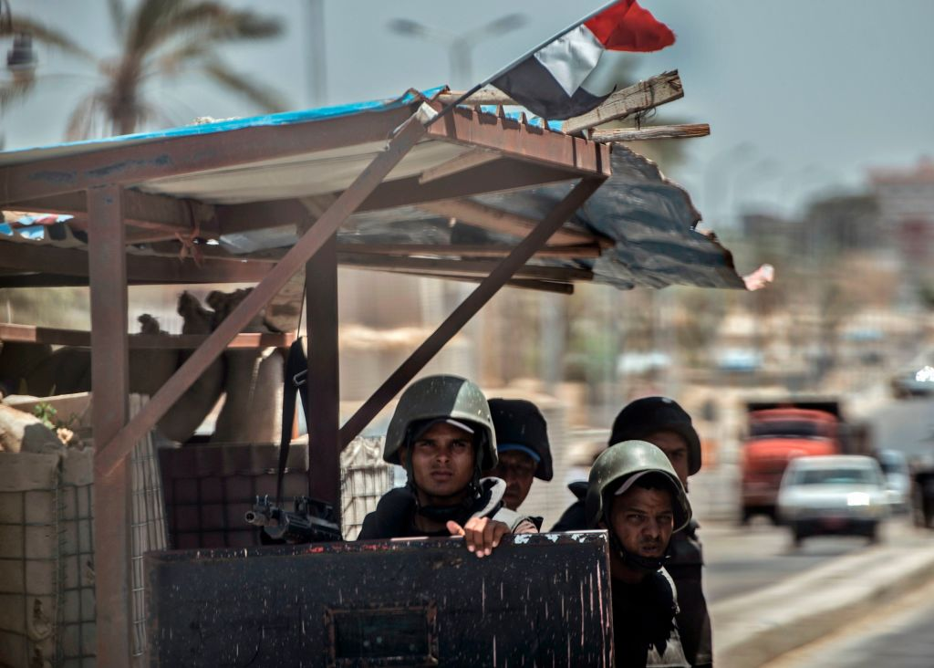 A picture taken on July 26, 2018, shows Egyptian policemen stand guarding a checkpoint on a road leading to the North Sinai provincial capital of El-Arish. With fruit and vegetables aplenty in the markets, public transport back on the roads and universities reopened, life is returning to El-Arish in North Sinai state where Egypt's army is at war with jihadists. (Khaled Desouki/AFP via Getty Images)