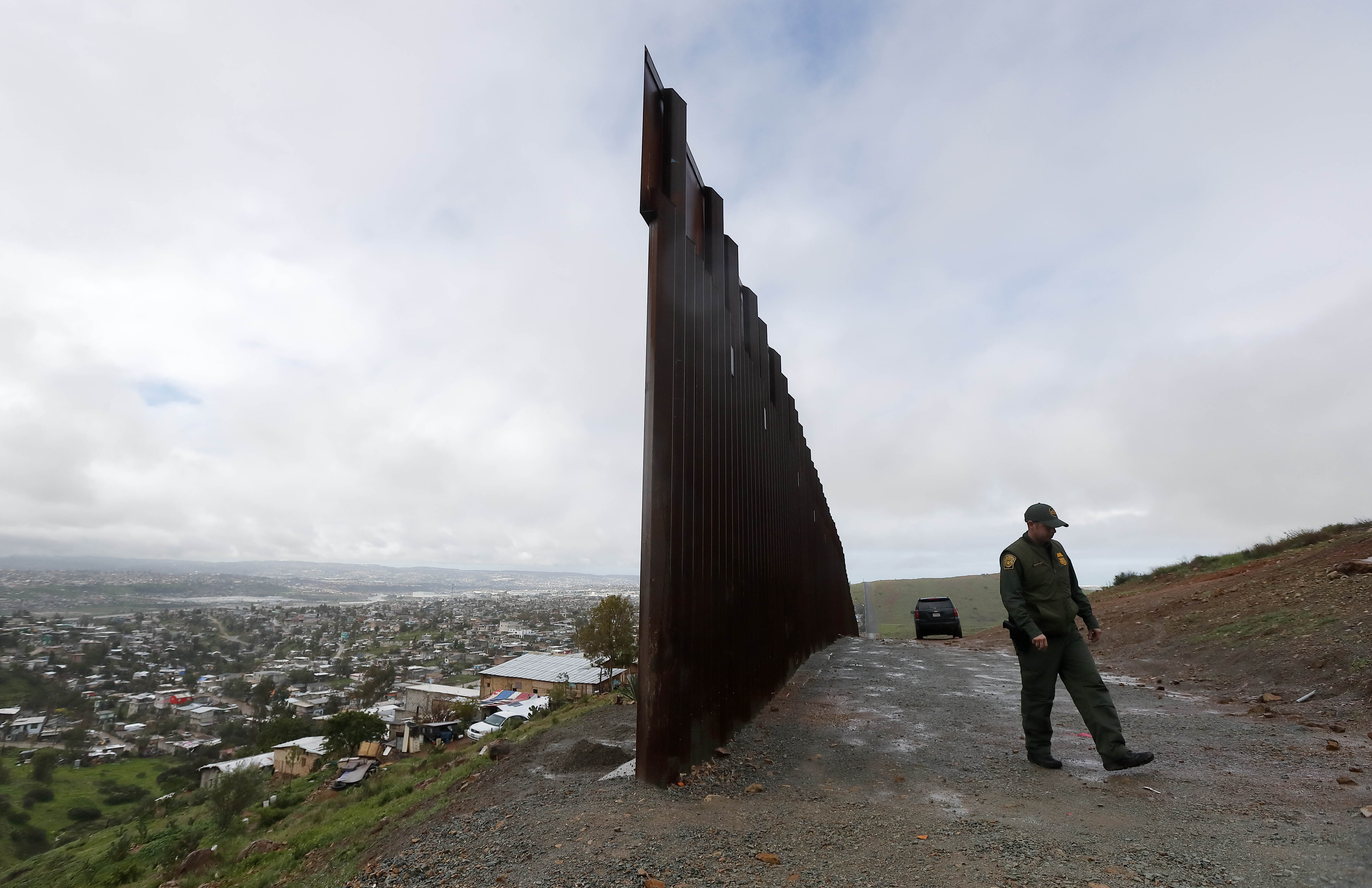 Border Patrol agent Vincent Pirro walks near the end of a border wall ends that separates Tijuana, Mexico, left, from San Diego, right, on Feb. 5, 2019. On Friday, President Donald Trump announced he will declare a national emergency on immigration, allowing him to use military construction funds to build more miles of the border wall despite resistance to the proposal from lawmakers. (Gregory Bull/AP)