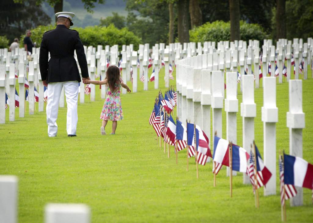 A U.S. Marine walks with a small girl through headstones prior to a Memorial Day commemoration at the Aisne-Marne American Cemetery in Belleau, France, Sunday, May 27, 2018. The cemetery contains more that 2,000 American dead. (Virginia Mayo/AP)