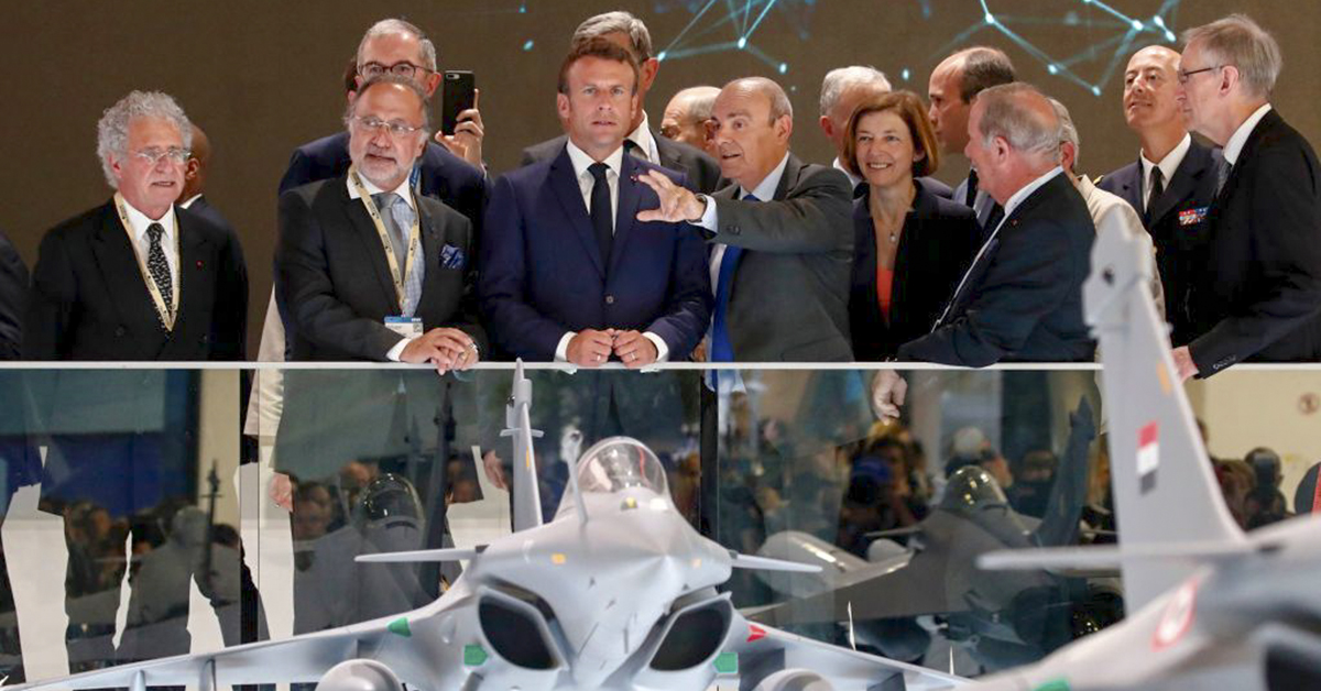 French President Emmanuel Macron, center, listens to Eric Trappier, chairman and CEO of Dassault Aviation, as he stands next to French MP Olivier Dassault, second from left, and French Armed Forces Minister Florence Parly at the Paris Air Show on June 17, 2019. (Benoit Tessier/AFP via Getty Images)