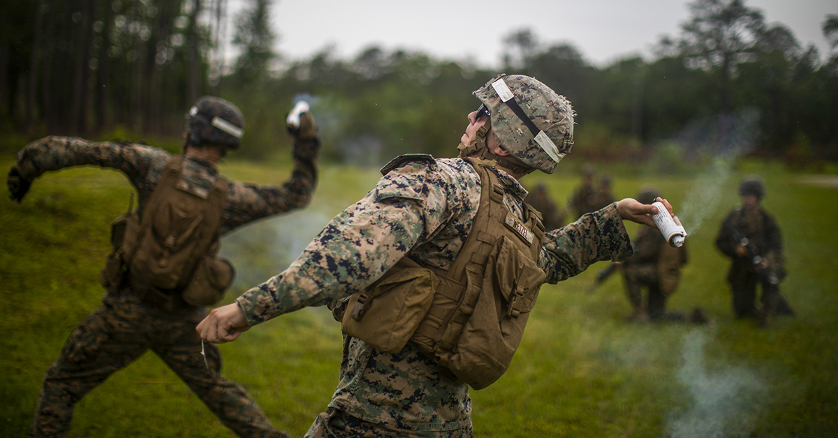 Marine Sgt. Nicholas R. Wetzel, a combat instructor assigned to Kilo Company, Marine Combat Training Battalion, School of Infantry-East, throws a ground burst projectile simulator C1A1 during a live fire and maneuver exercise at Camp Lejeune, North Carolina. (Sgt. James R. Skelton/Marines)