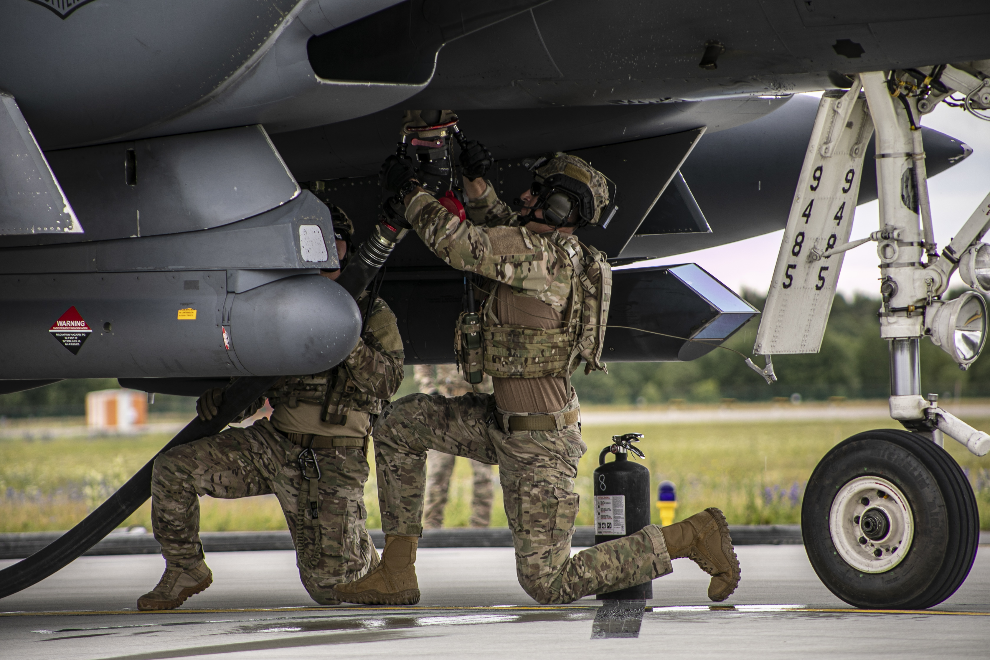 Two U.S. Air Force logistics readiness airmen attach a fuel nozzle underneath an F-15E Strike Eagle during a forward air refueling point mission on July 16, 2019, at Amari Air Base, Estonia. (Sgt. Alexis Washburn-Jasinski/U.S. Army)