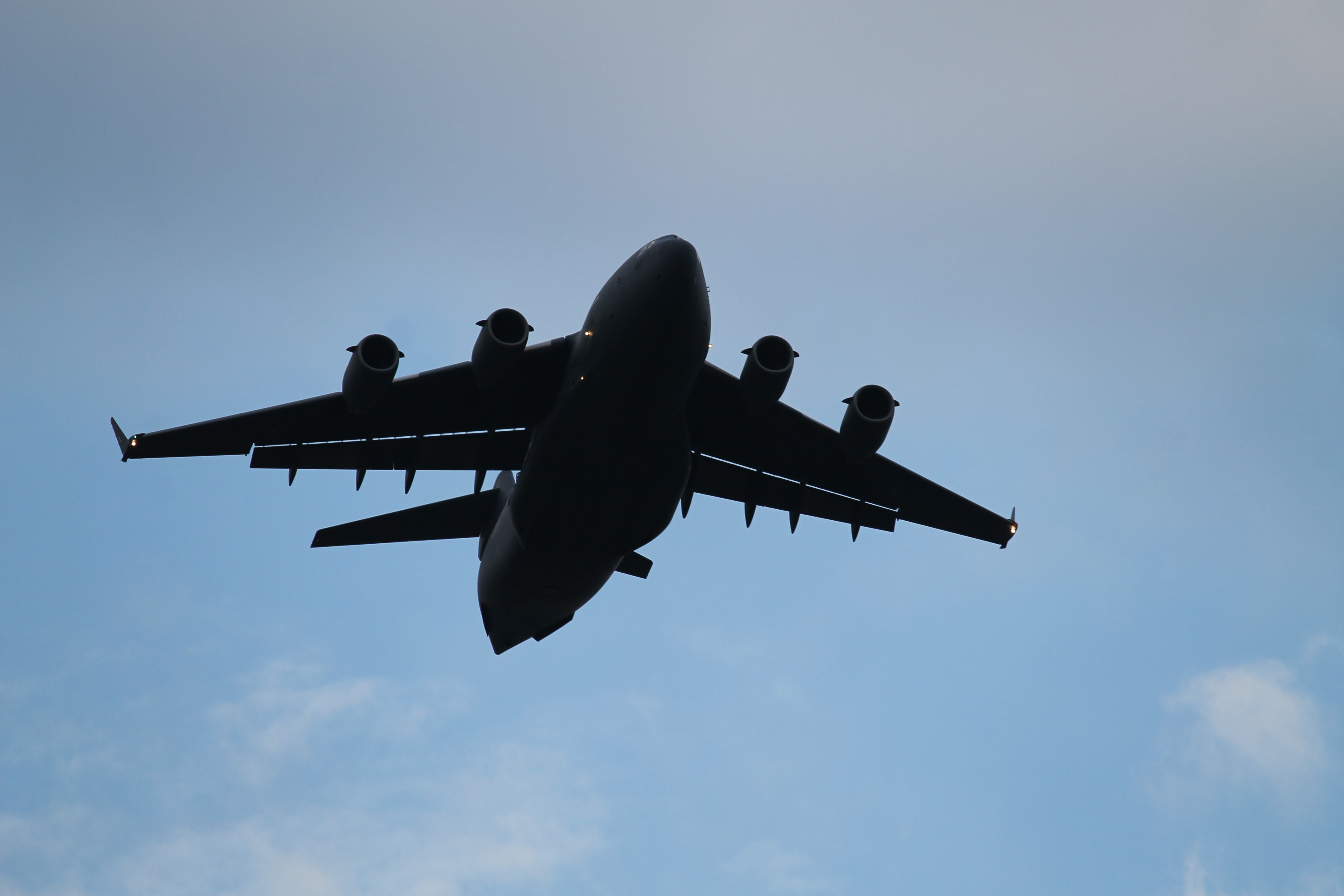 A C-17 flies over a drop zone at Bezmer Air Base, Bulgaria, at dusk on July 18. Eleven C-130s and two C-17s passed over the airfield, dropping paratroopers from the 173rd Airborne Brigade Combat Team based out of Vicenza, Italy, along with others from Portugal and Canada as part of Swift Response, an exercise within Saber Guardian. (Jed Judson/Staff)
