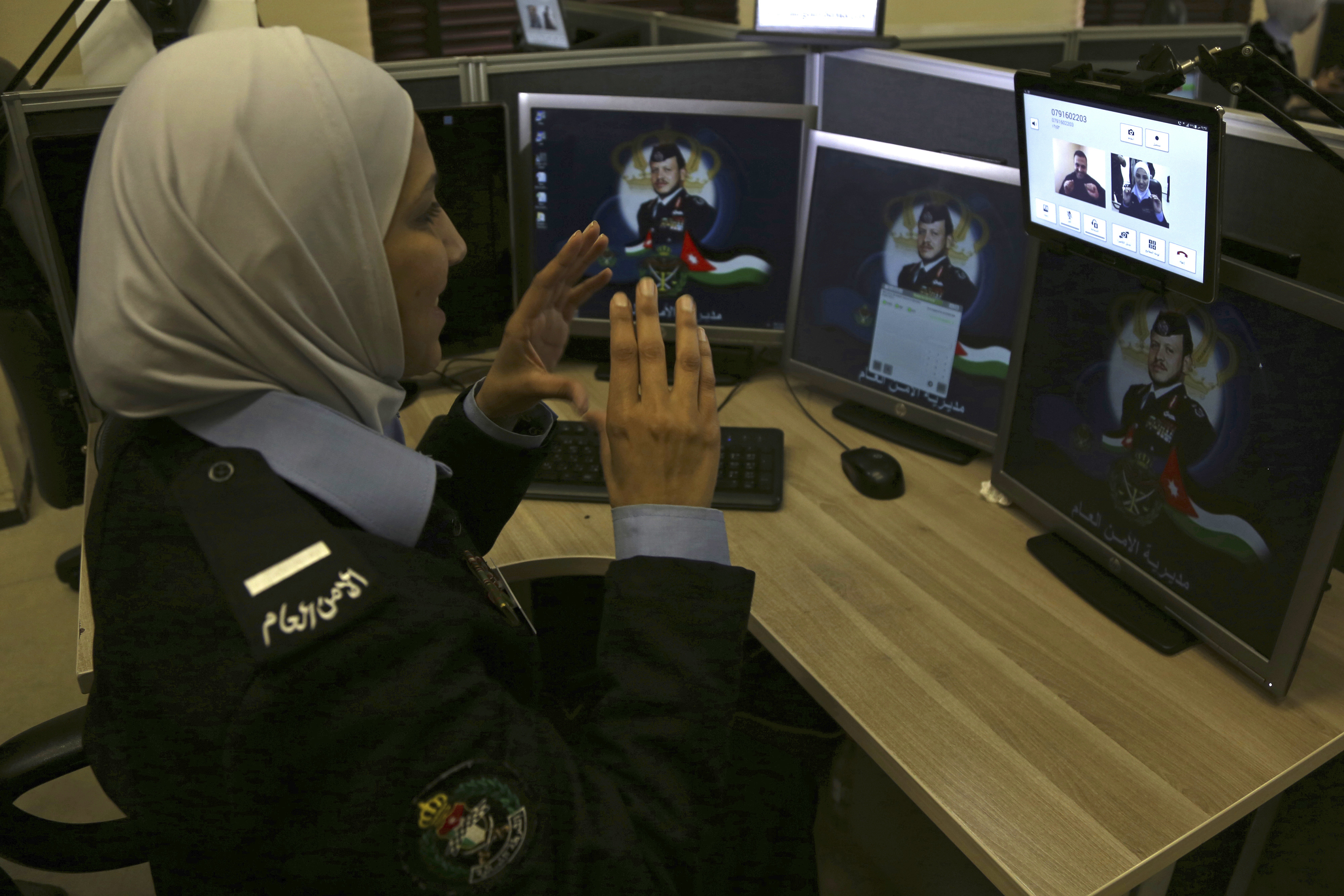 A dispatcher using sign language communicates with a hearing-impaired caller at Jordan's 911 emergency call center in the capital of Amman on March 20, 2018. The caller complained about what he said were undeserved traffic tickets. (Raad Adayleh/AP)