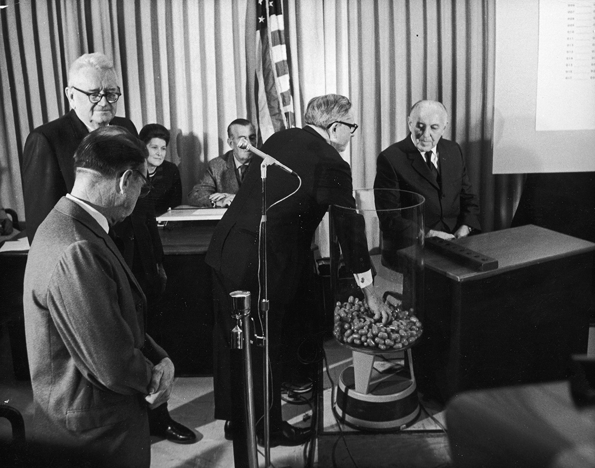 Rep. Alexander Pirnie, R-N.Y., reaches into the bowl to draw the first date in the draft lottery held at Selective Service Headquarters in Washington on Dec. 2, 1969, for the war in Vietnam. Looking on, from left: Col. W.P. Averill, Gen. Lewis Hershey, and Col. Daniel Omer. (AFP/Getty Images)