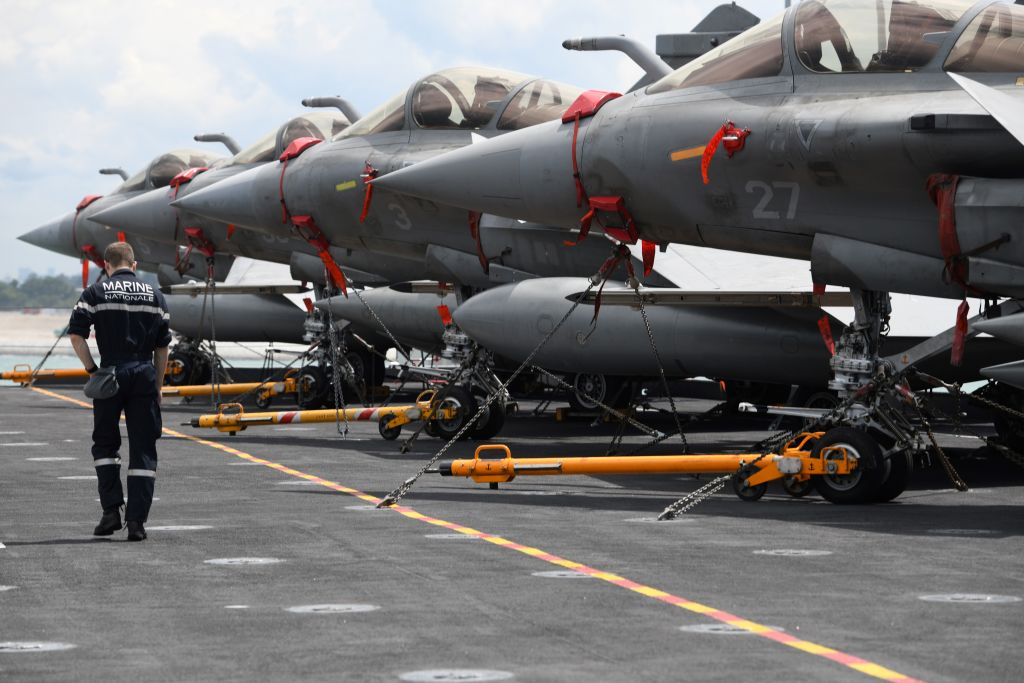 A crew member walks past a row of fighter jets Rafale parked on the flight deck of the French aircraft carrier Charles de Gaulle during a media tour at Changi Naval Base in Singapore on May 28, 2019. (ROSLAN RAHMAN/AFP/Getty Images)