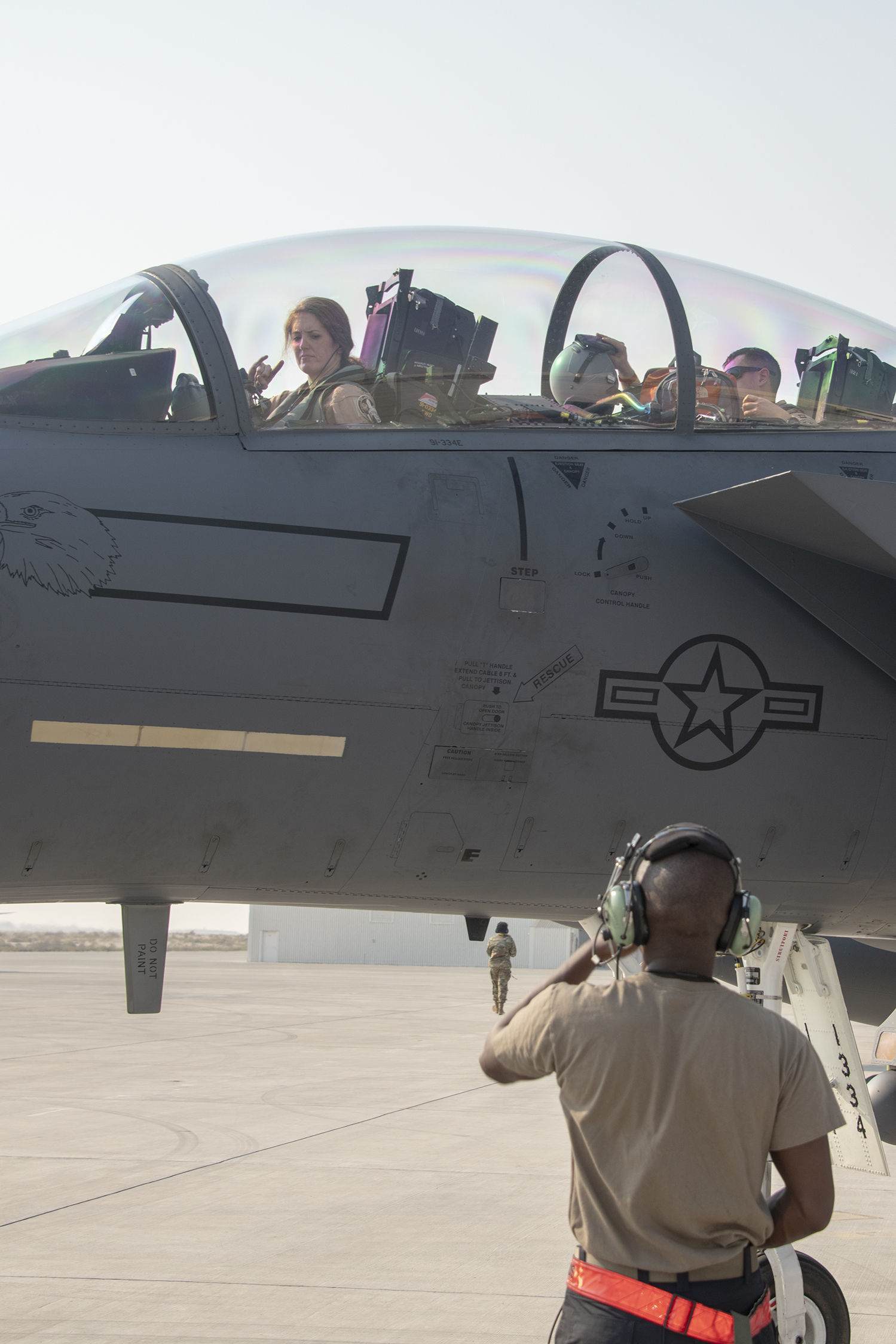 Lt. Col. Jaina Donberg, 494th Fighter Squadron commander, signals to a crew chief from the 380th Expeditionary Aircraft Maintenance Squadron, after parking Oct. 21, 2019, at Al Dhafra Air Base, United Arab Emirates. (Tech. Sgt. Kat Justen/Air Force)