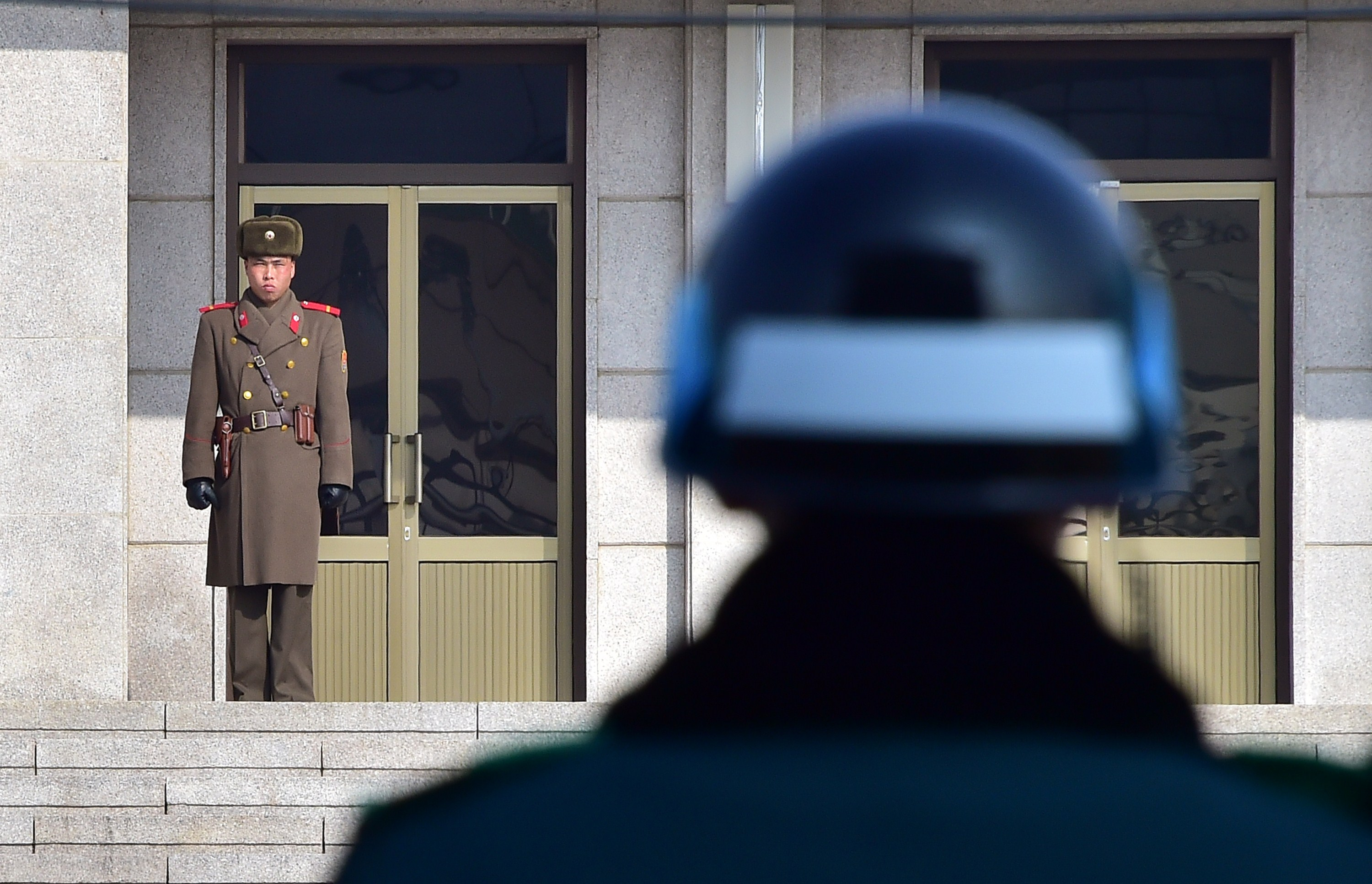 A North Korean soldier (L) and a South Korean soldier (R) stand opposite each other at the truce village of Panmunjom in the Demilitarized Zone dividing the two Koreas. (Jung Yeon-Je/AFP/Getty Images)