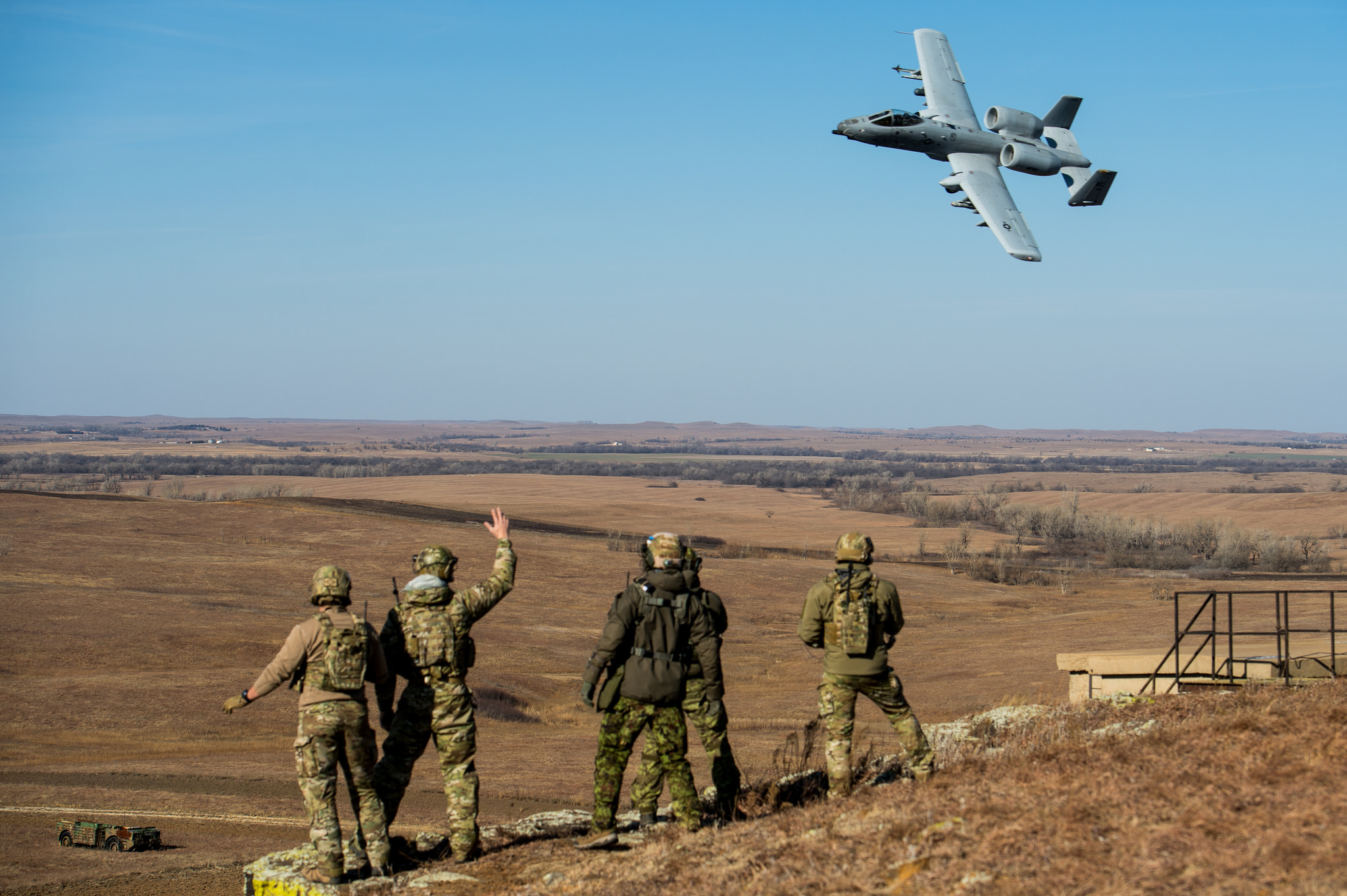 Members of the Oklahoma National Guard's 146th Air Support Operations Squadron and Estonian tactical air control party specialists acknowledge an A-10 Thunderbolt II during a show of force after completing close-air support training at Smoky Hill Air National Guard Range in Salina, Kan., Dec. 13, 2017. The Estonian TACPs traveled to the U.S. to work alongside members of the 146 ASOS to complete upgrade training and enhance multi-national relationships. This was the first time the 146 ASOS hosted the Estonian TACPs. (Sgt. Tyler Woodward/Air National Guard)