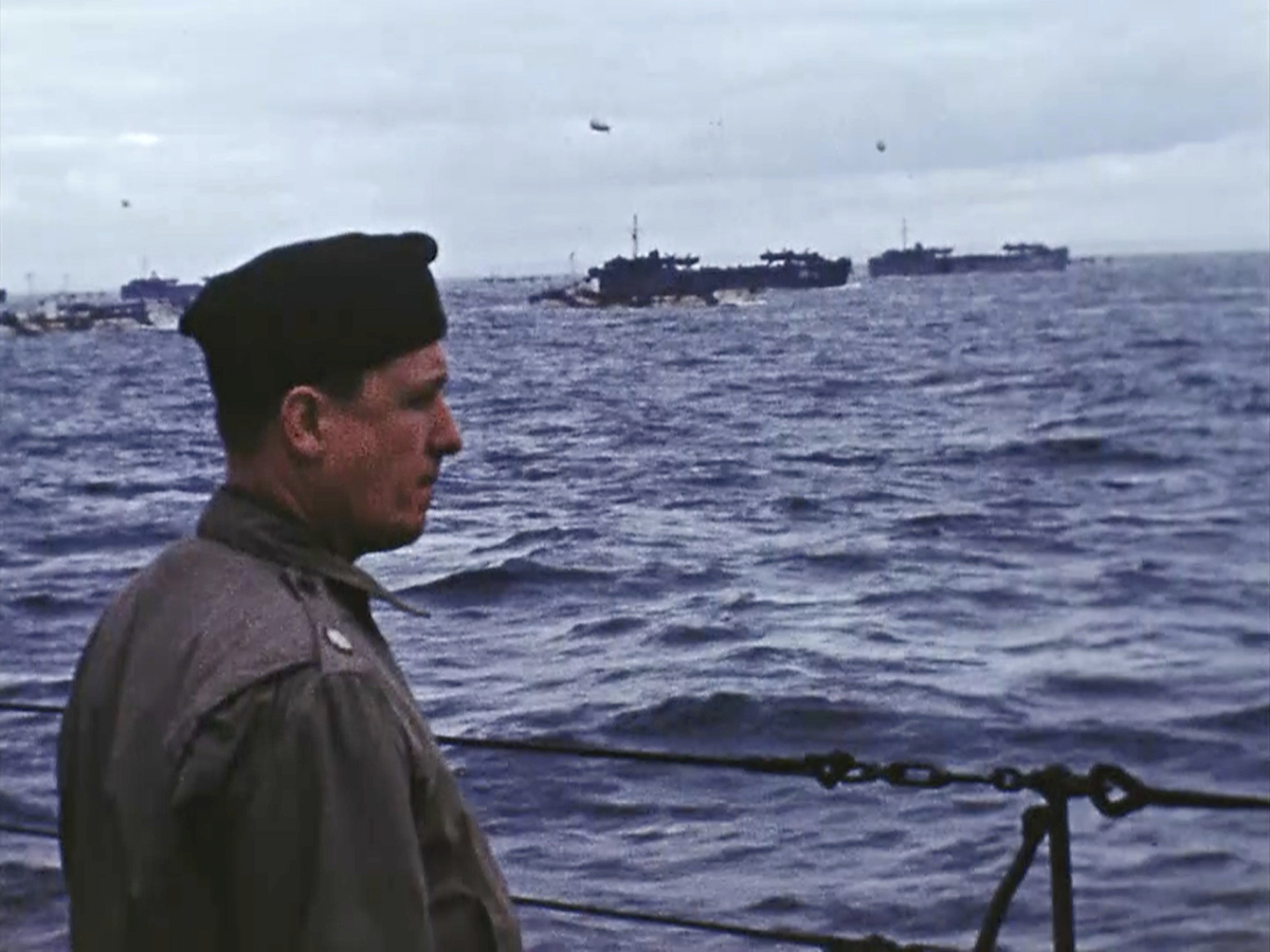 Hollywood director George Stevens stands on a ship off the coast of France on D-Day, June 6, 1944. Seventy-five years later, surprising color images of the D-Day invasion and aftermath bring an immediacy to wartime memories. They were filmed by Hollywood director George Stevens and rediscovered years after his death. (War Footage From the George Stevens Collection at the Library of Congress via AP)