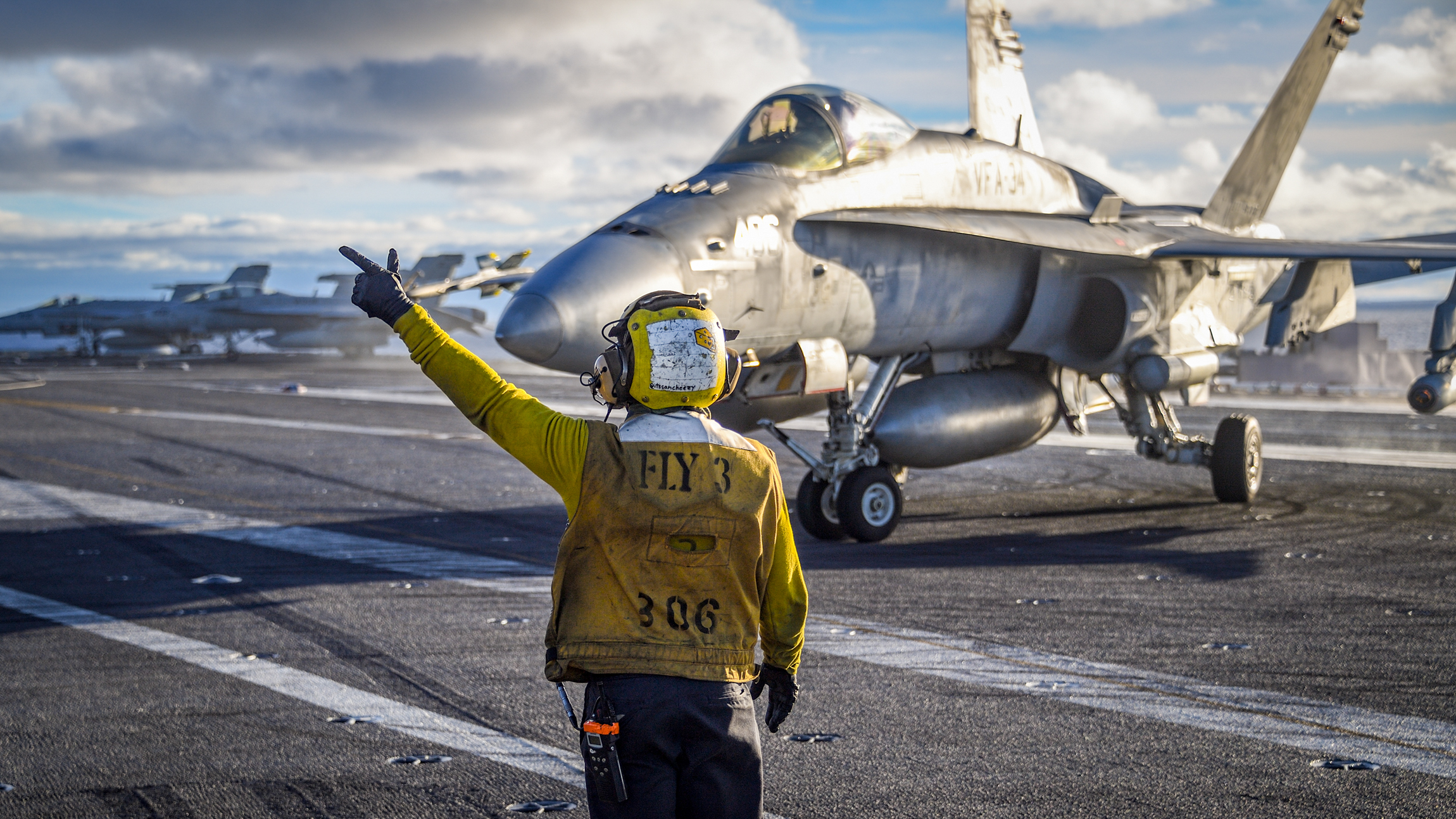 """Aviation Boatswain's Mate (Handling) 3rd Class Vincent Sanchez directs the pilot of an F/A-18C Hornet from the """"Blue Blasters"""" of Strike Fighter Squadron (VFA) 34 on the Nimitz-class aircraft carrier USS Carl Vinson flight deck. Carl Vinson is participating in a sustainment training exercise in preparation for an upcoming deployment. (MC2 Sean M. Castellano/Navy)"""