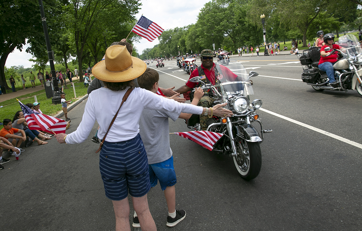 A rider slaps hands with some of the supporters who came out to line the route along Constitution Ave. during Rolling Thunder XXXI First Amendment Demonstration Run in Washington, DC on Sunday May 27, 2018. Motorcycle riders from across the nation, rode a designated route through the Mall area of Washington, D.C. The event is an actual demonstration/protest to bring awareness and accountability for POWs and MIAs left behind.(Alan Lessig/Staff)