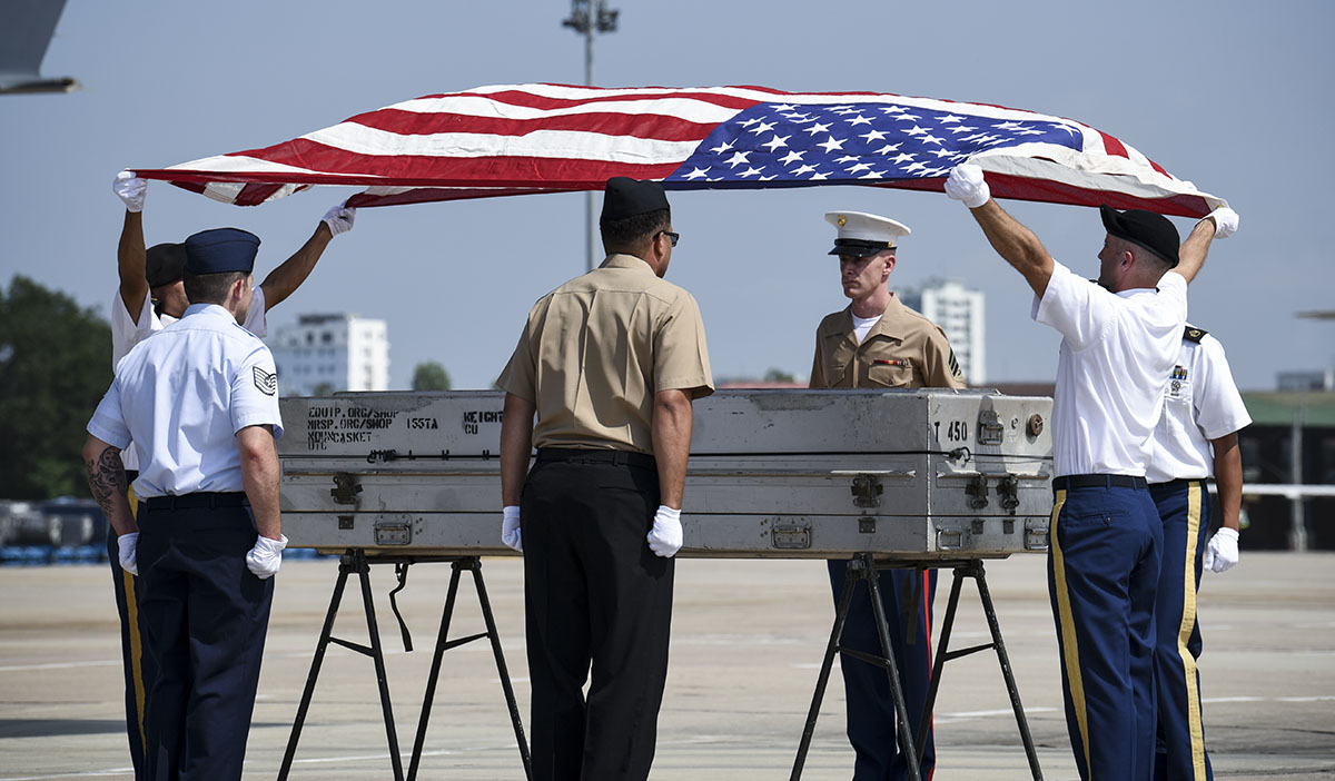 Service members assigned to the Defense POW/MIA Accounting Agency drape the U.S. flag over a transfer case during a repatriation ceremony in Vietnam on April 15. (Sgt. 1st Class David J. Marshall/Army)